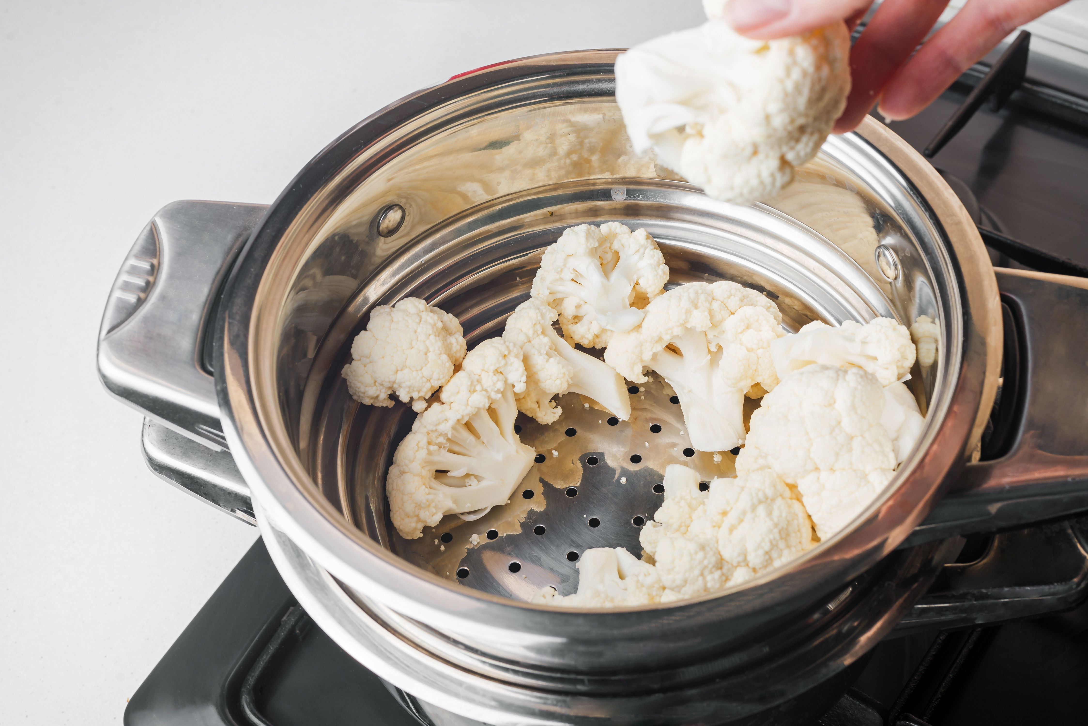 Hand placing cauliflower florets into steaming basket