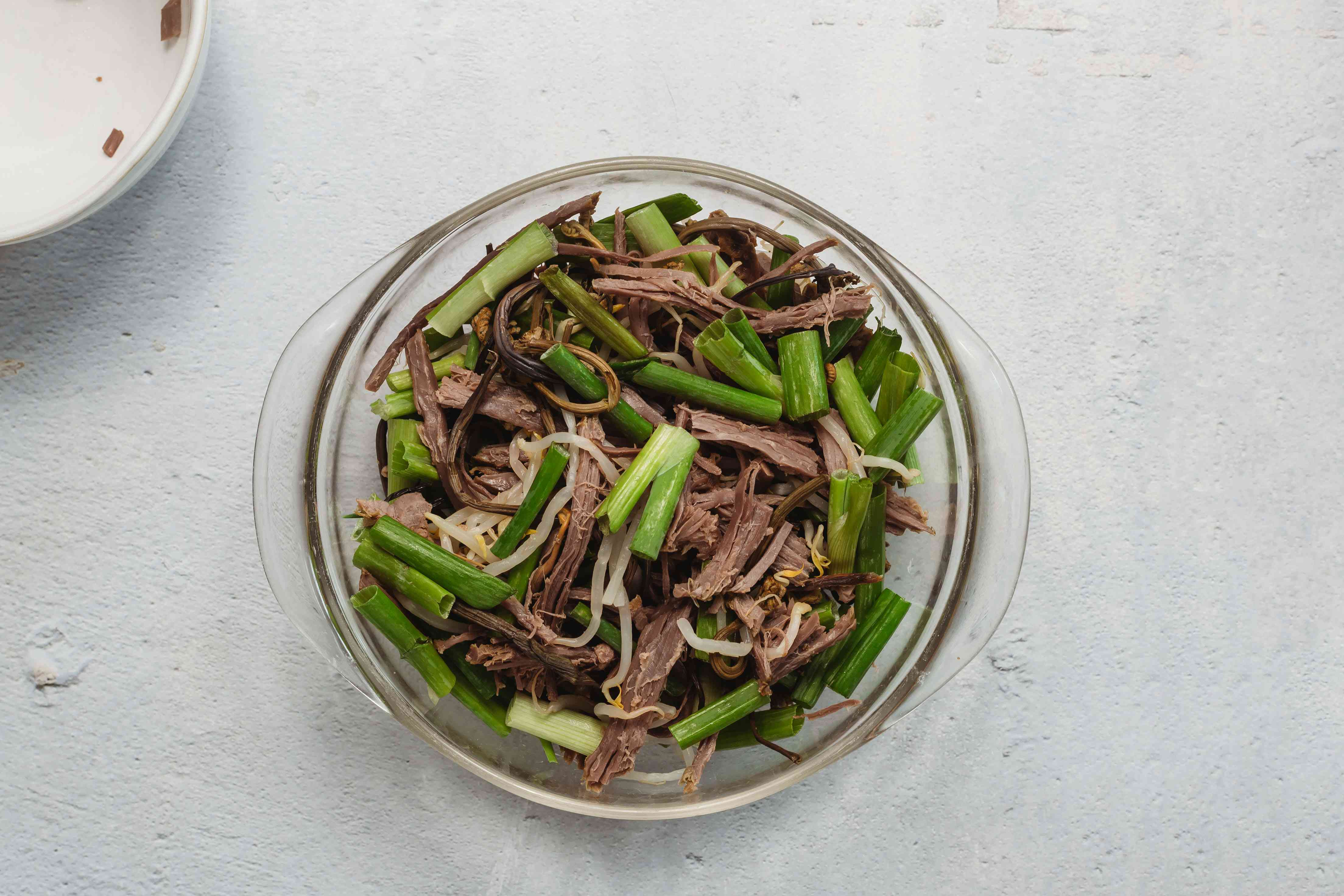 Shredded beef in a bowl with scallions and sprouts