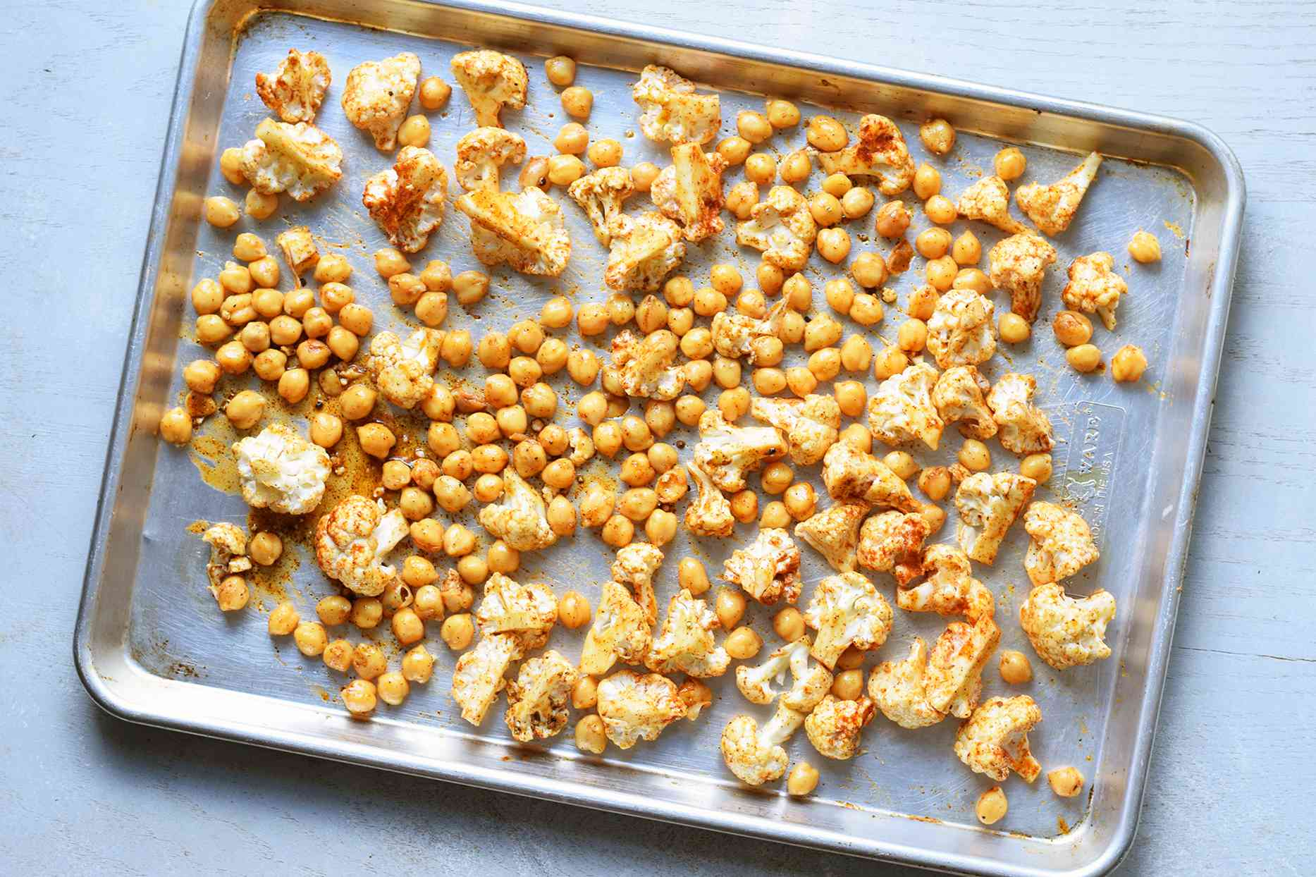 cauliflower and chickpeas spread on a sheet pan
