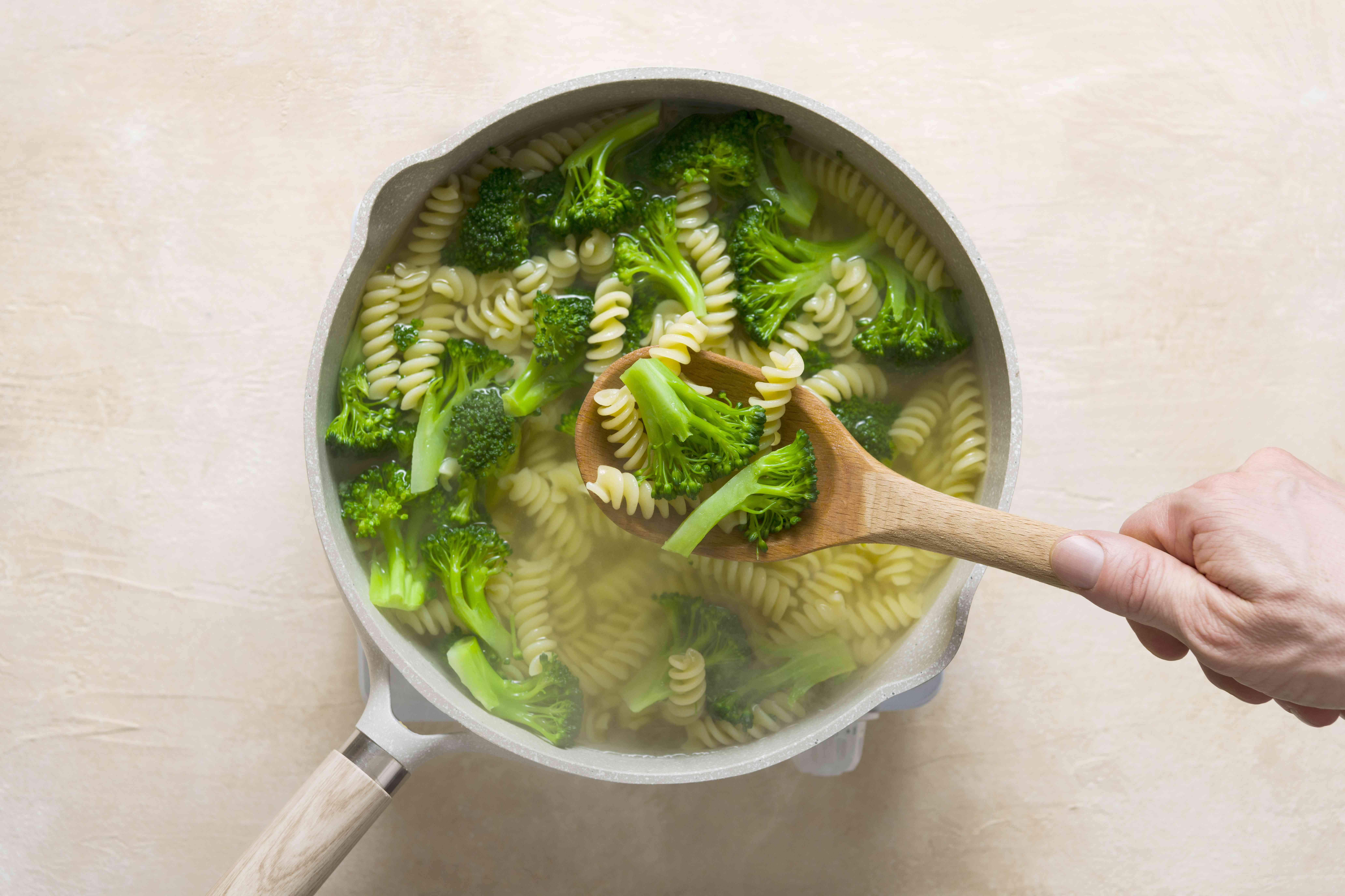 noodles and broccoli in a pot, removed with spoon