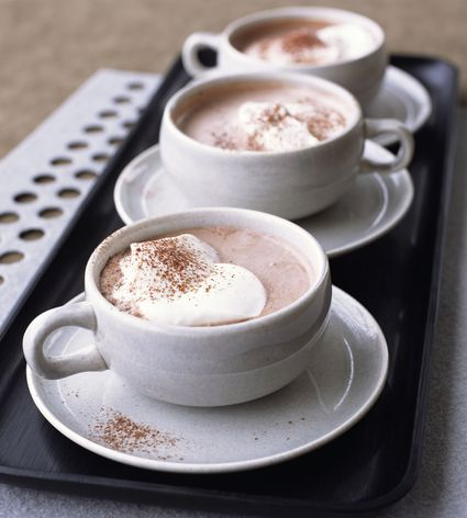 Hot cocoa with whipped cream in three mugs