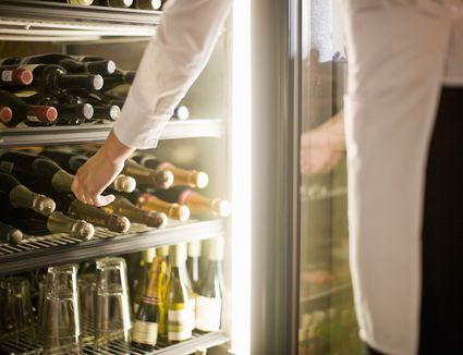 Woman reaching for bottle on wine in fridge