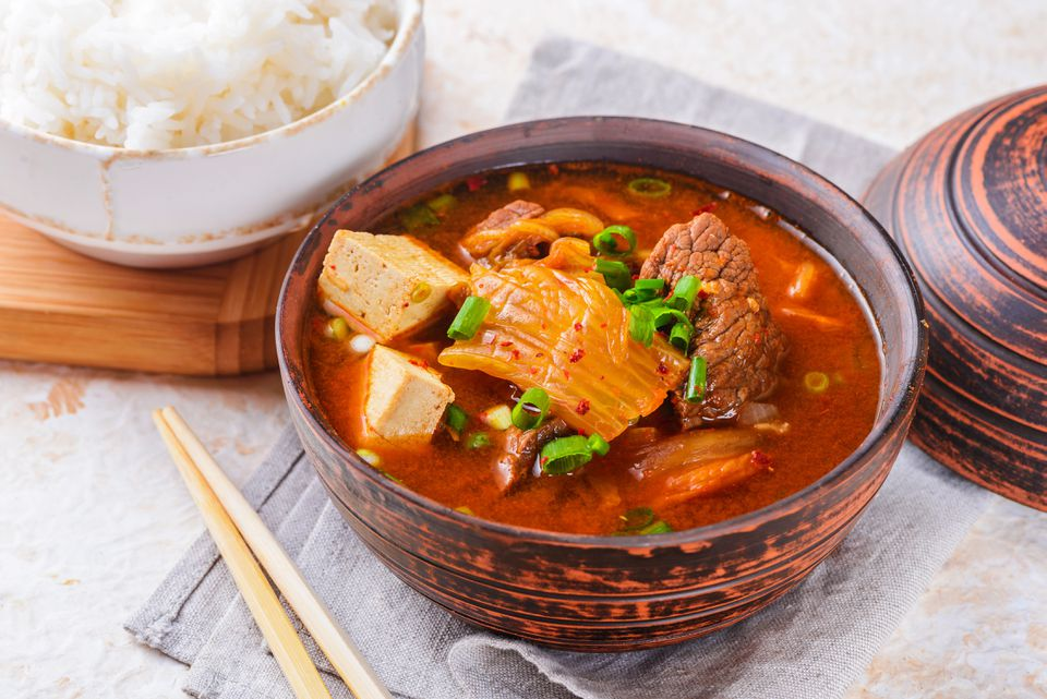 Spicy kimchi stew in a bowl with chopsticks
