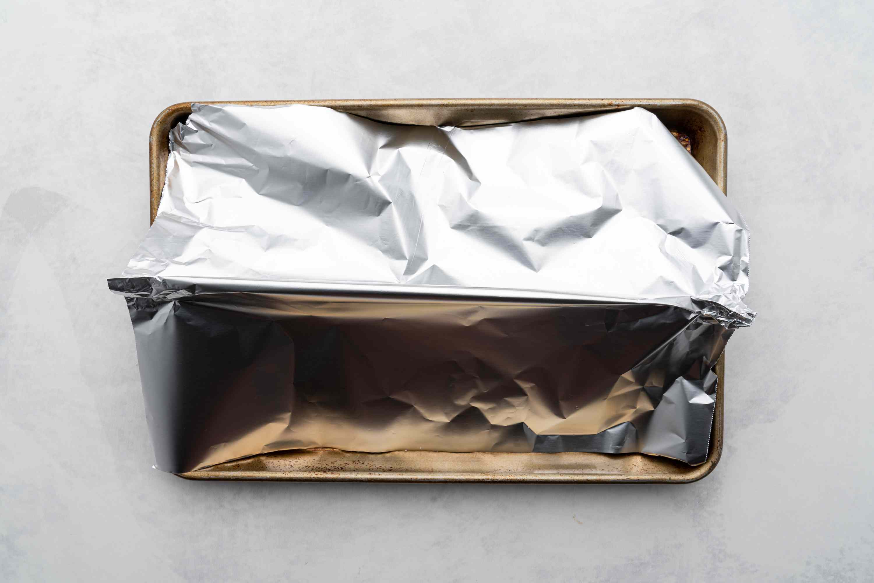 steak resting on sheet tray with foil tent covering meat