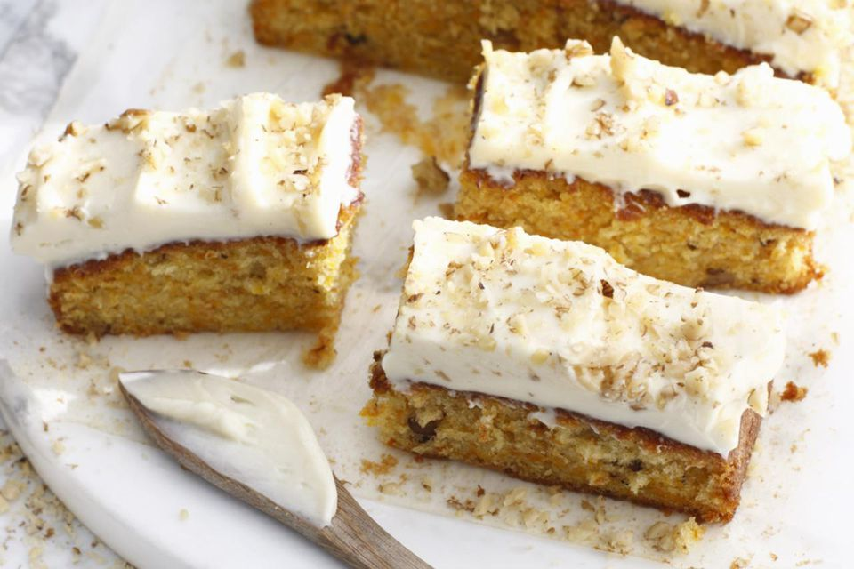 Platter of frosted carrot cake on a white background