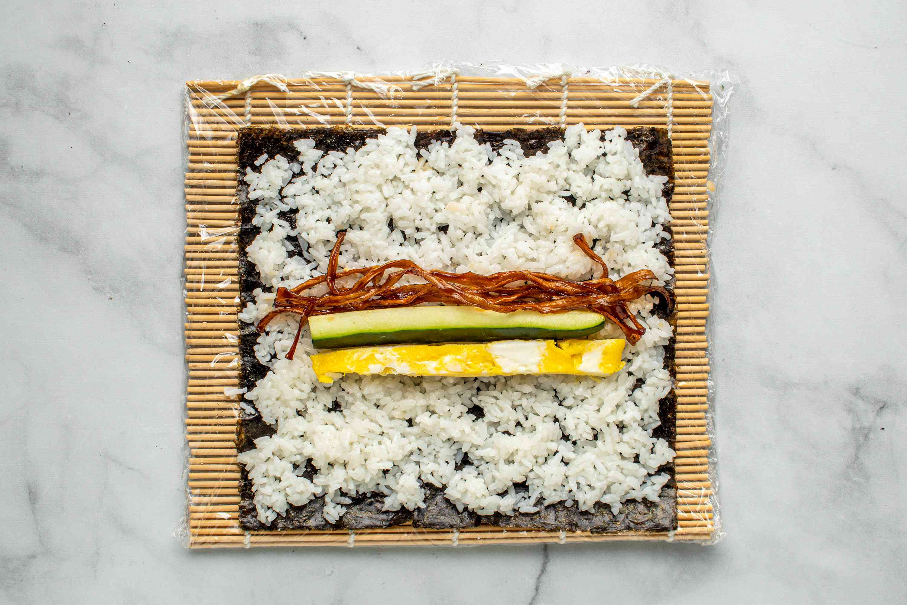 Place kanpyo, omelet, and cucumber sticks horizontally on rice in the center