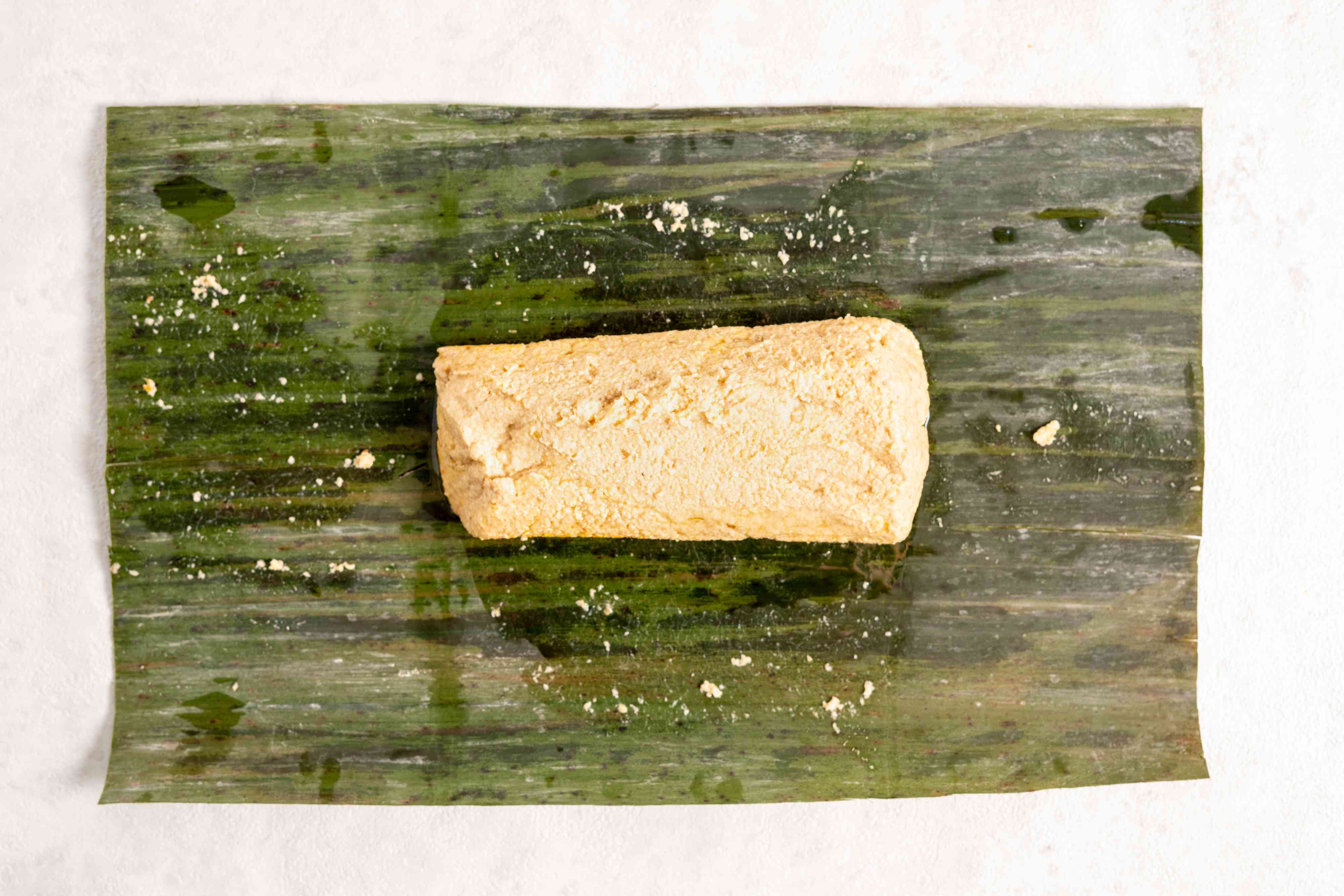 use the banana leaf to wrap the masa around the pork filling