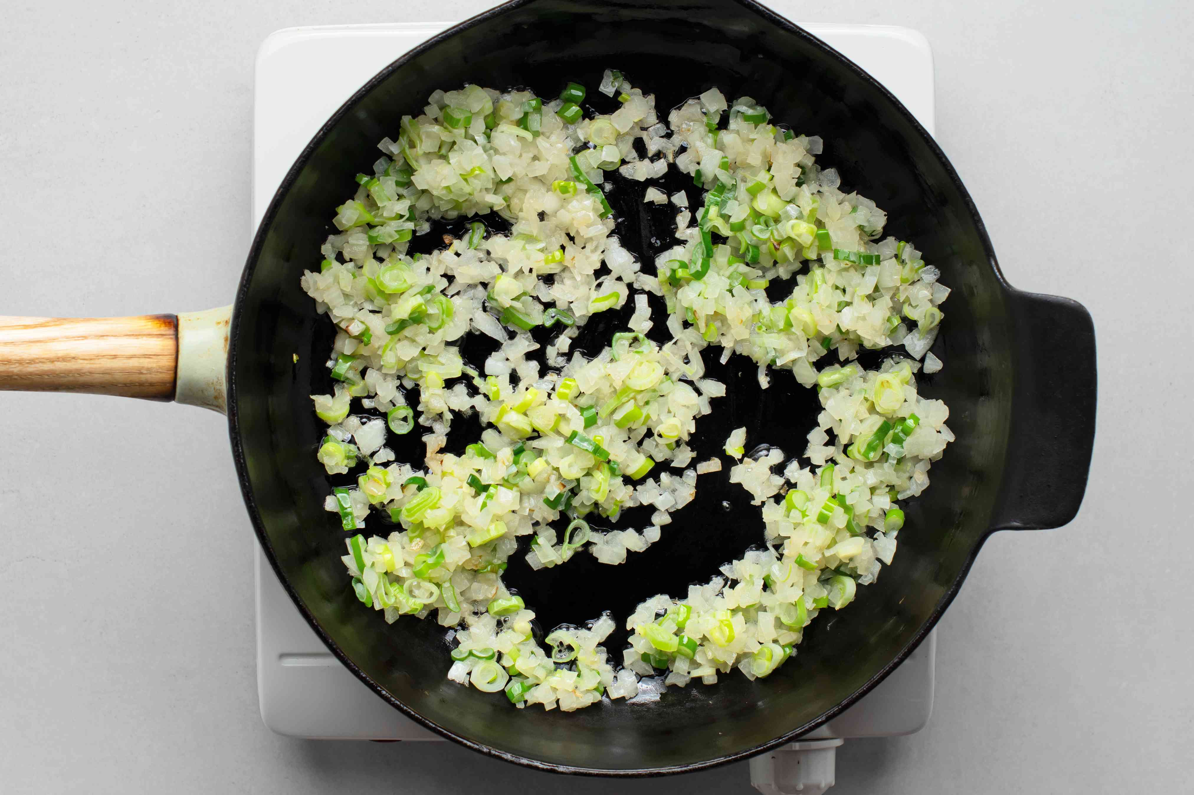 Onions and green onions cooking in a skillet with oil