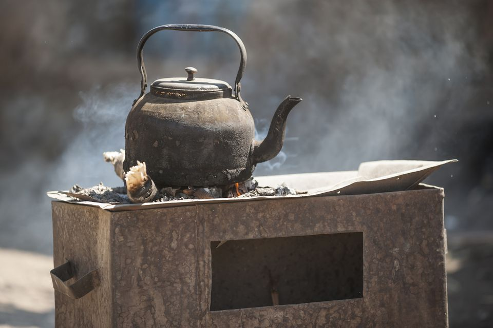 A rustic coffee kettle on a stove