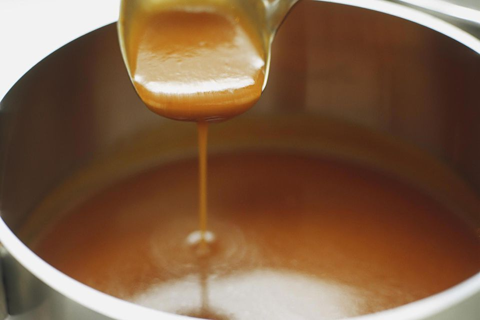 Brown sauce being ladled out of saucepan