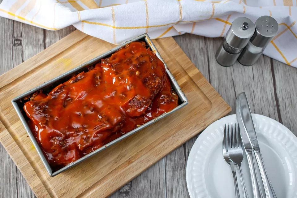 Meatloaf in a loaf pan with topping.