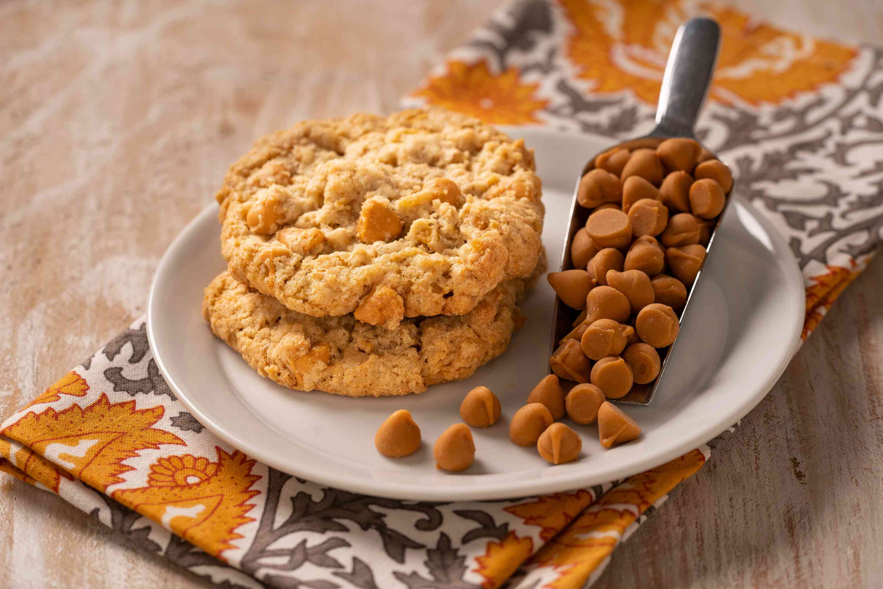 Butterscotch cookies on a serving plate with a scoopful of butterscotch chips on the side