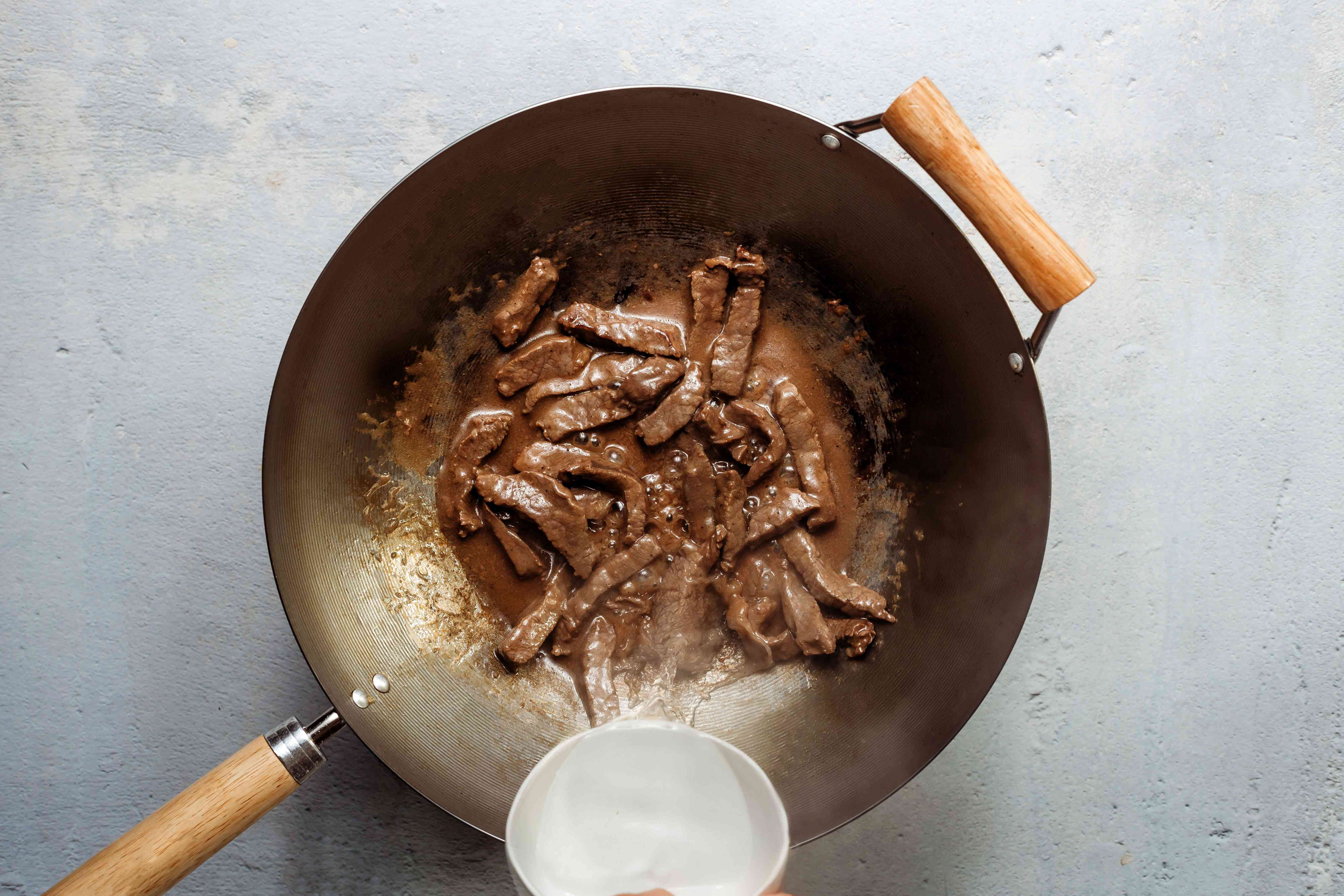 add water to the beef in the wok to form a gravy