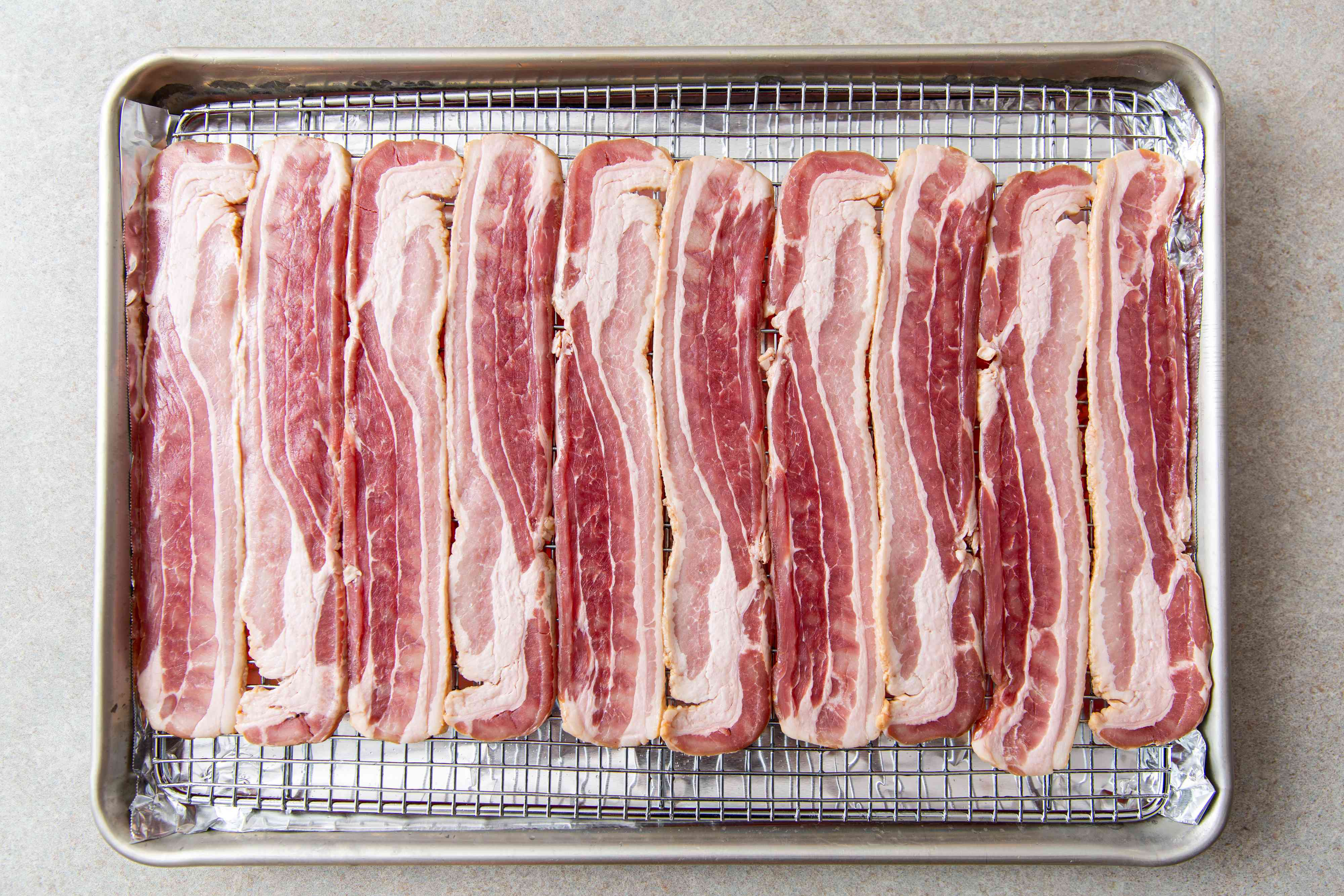 Raw bacon strips on a wire rack on a sheet pan
