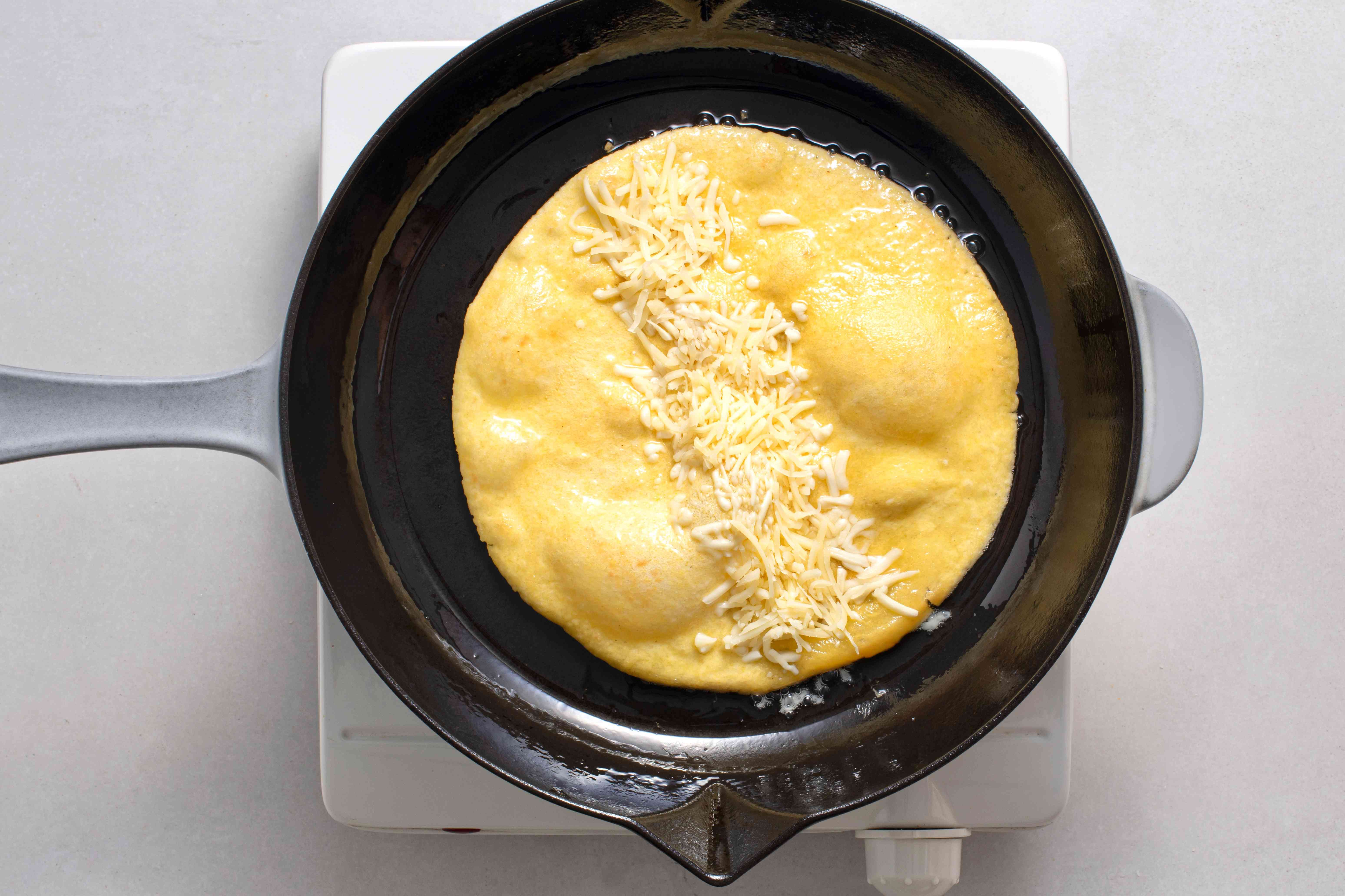 tortilla in a frying pan with cheese on top