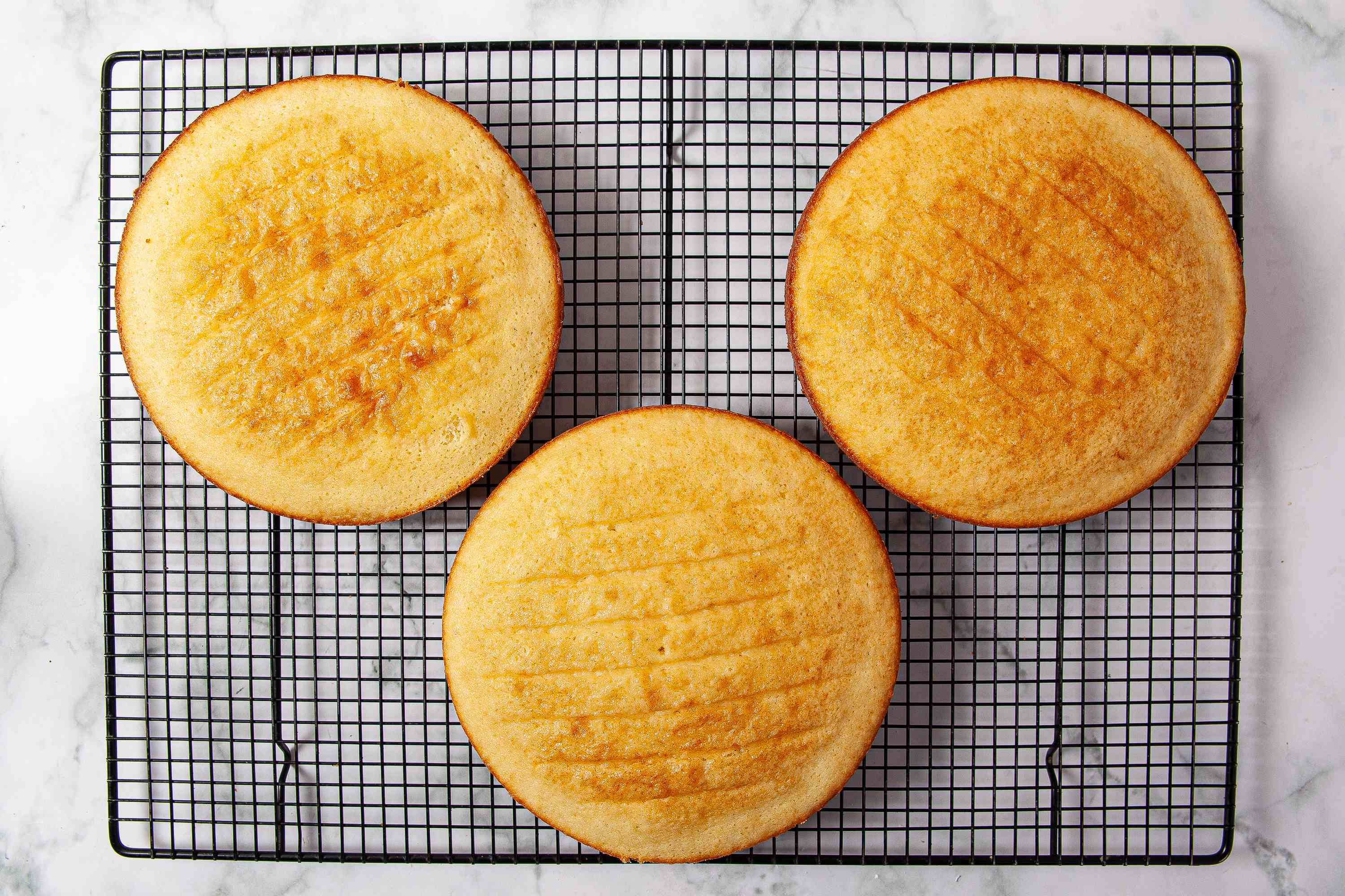 Three round cakes cooling on a wire rack