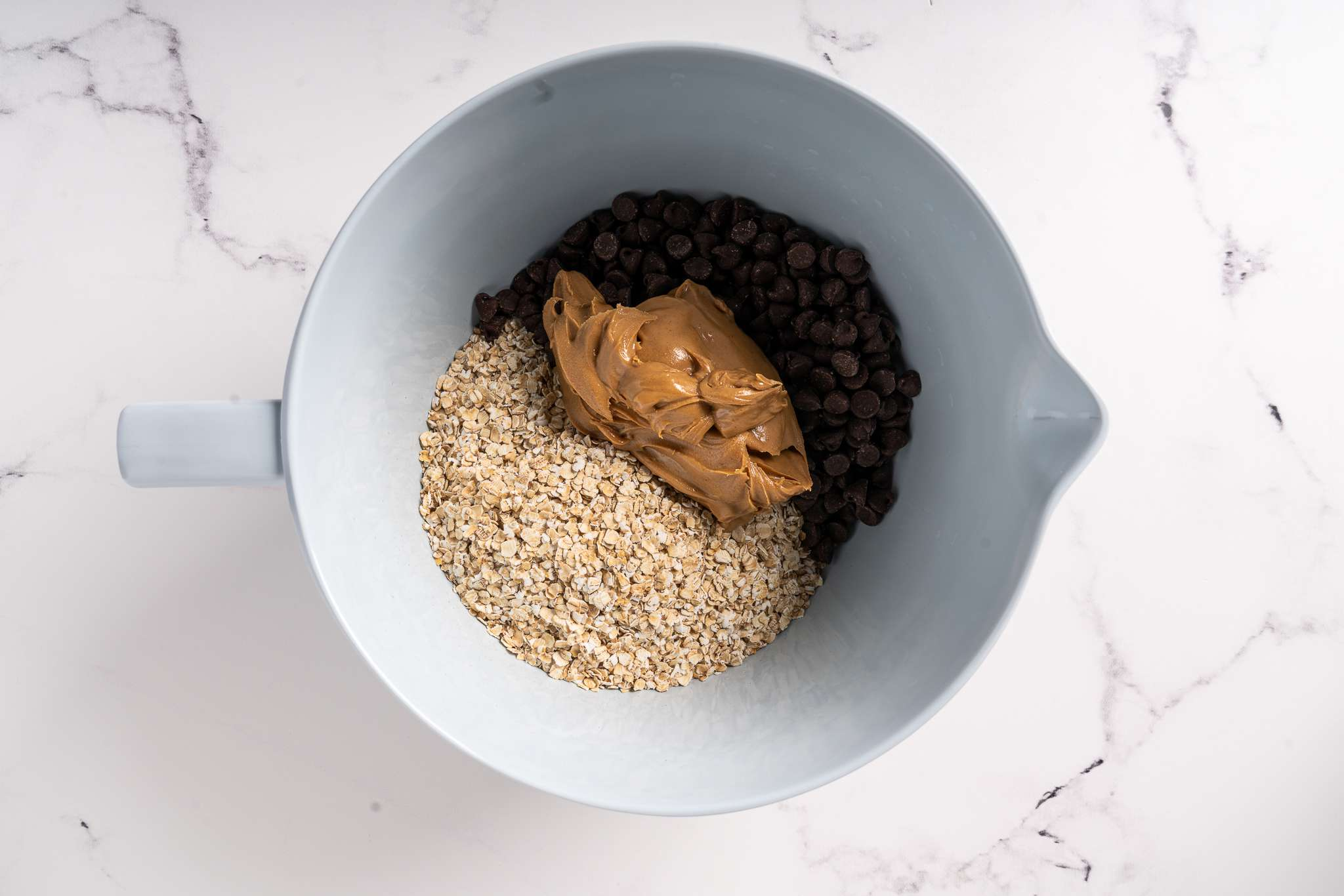 Oats, chocolate chips, vanilla, and peanut butter in a bowl