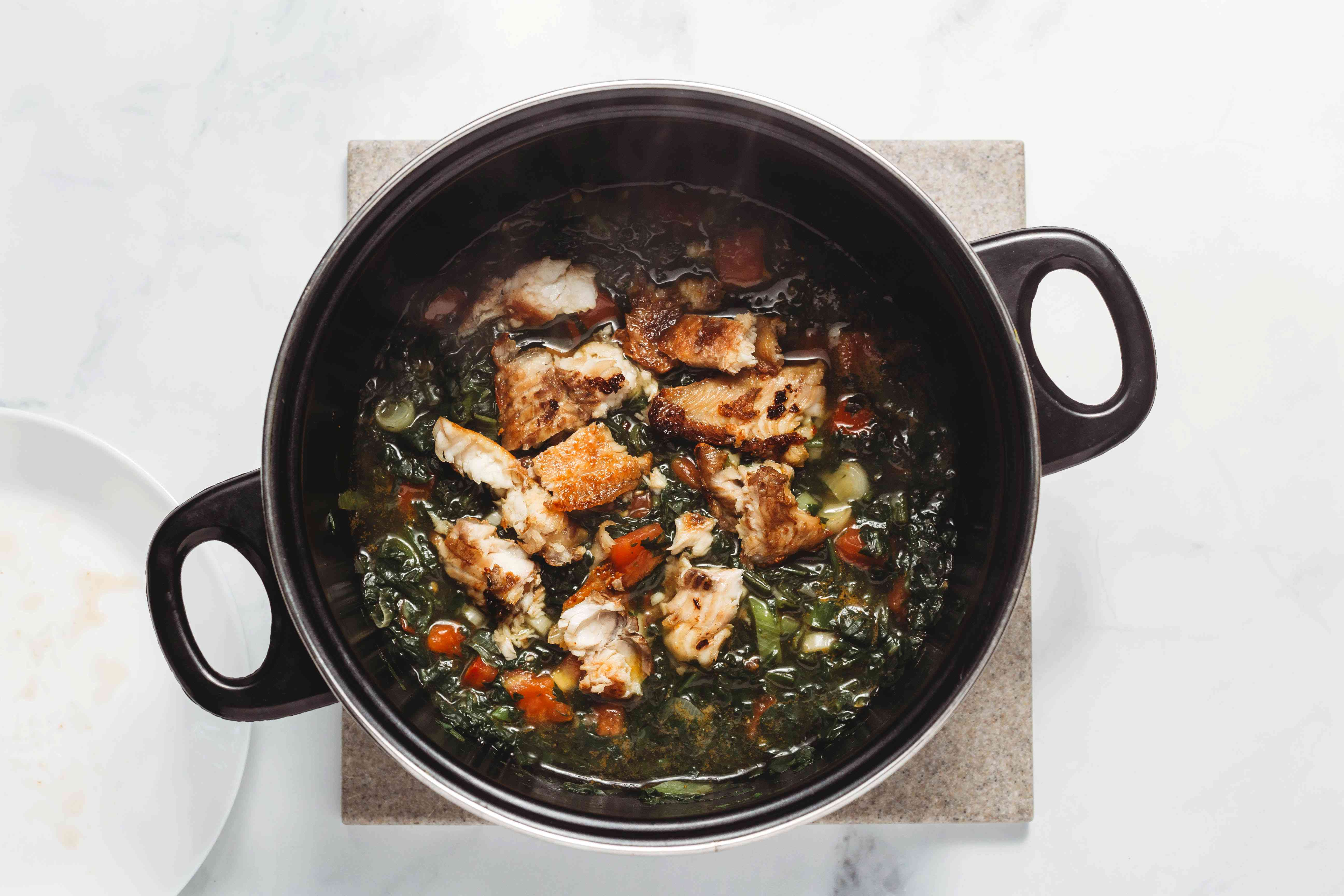 smoked fish in a large pot with spinach, tomatoes, onions, garlic and water