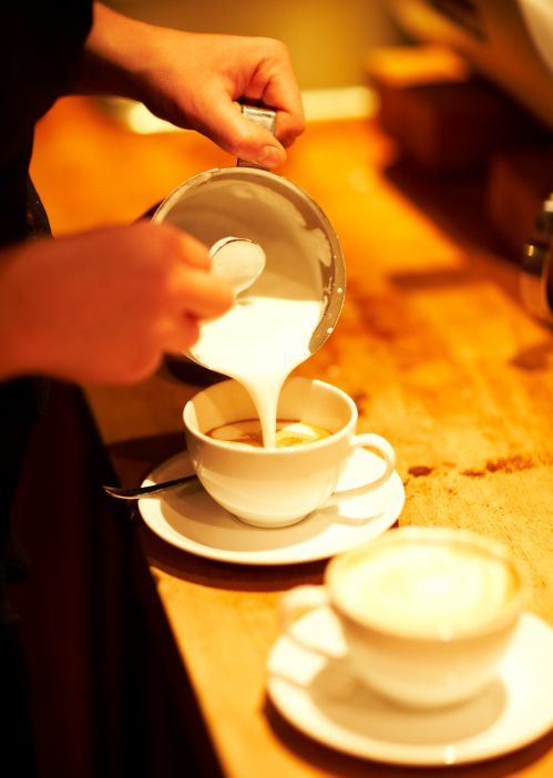 Hands pouring steamed milk into coffee cup