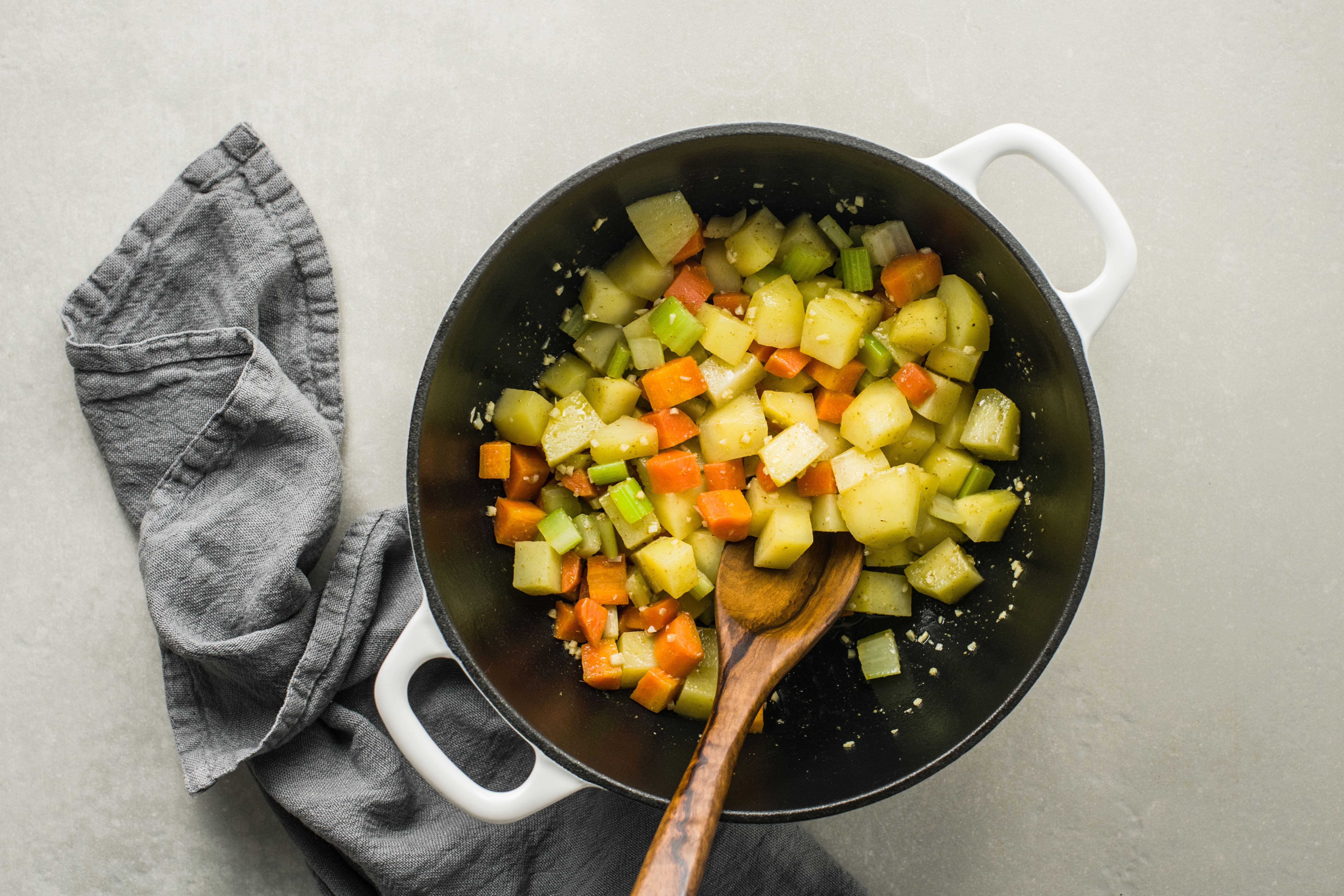Vegetables in pot with wooden spoon