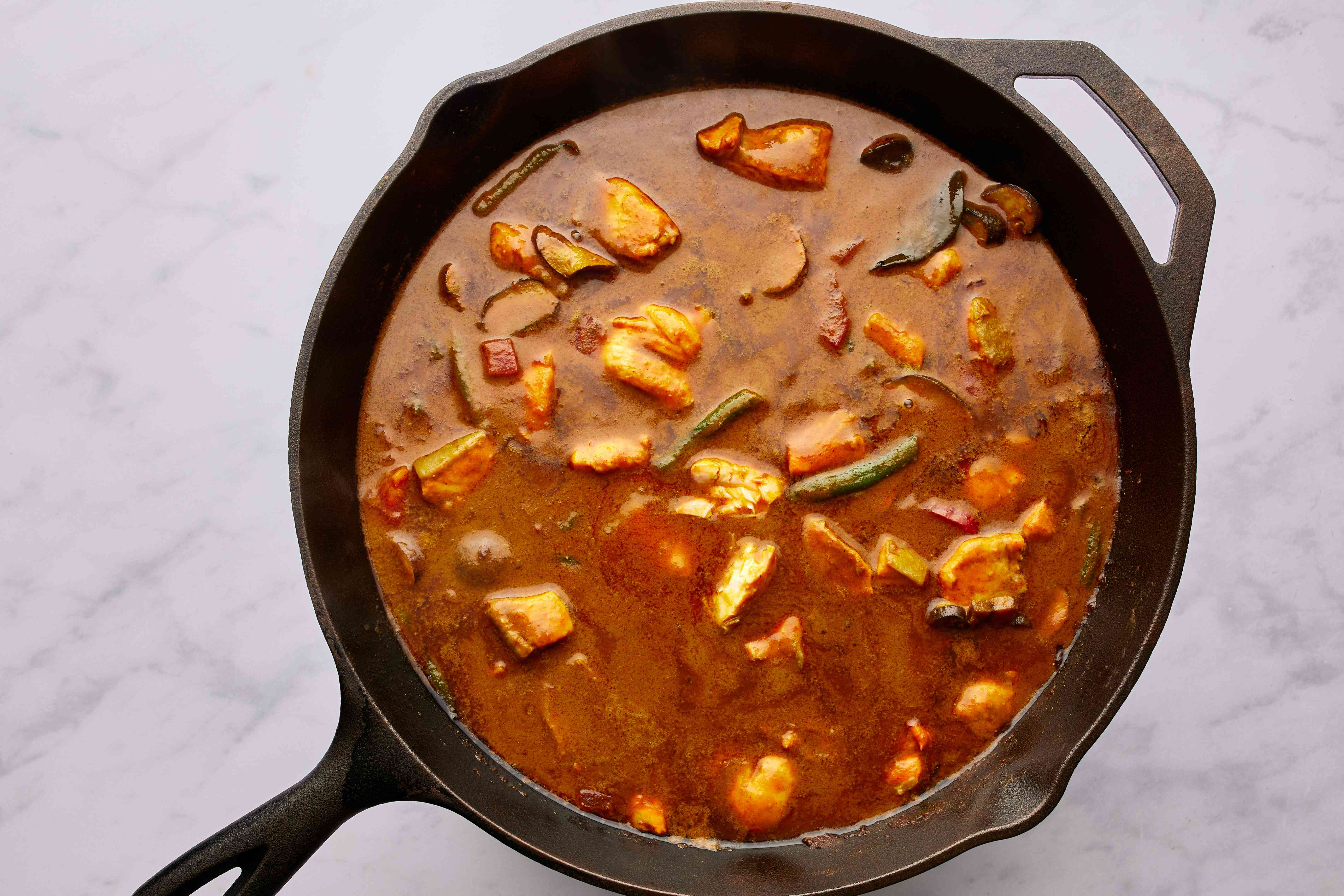 fish and tomato with curry sauce and vegetables in a pan