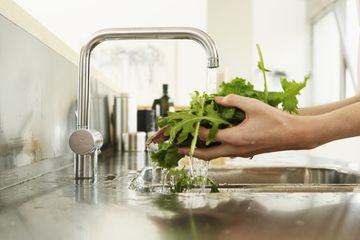 Close-up of hands rinsing greens under water