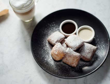 beignets on plate with coffee