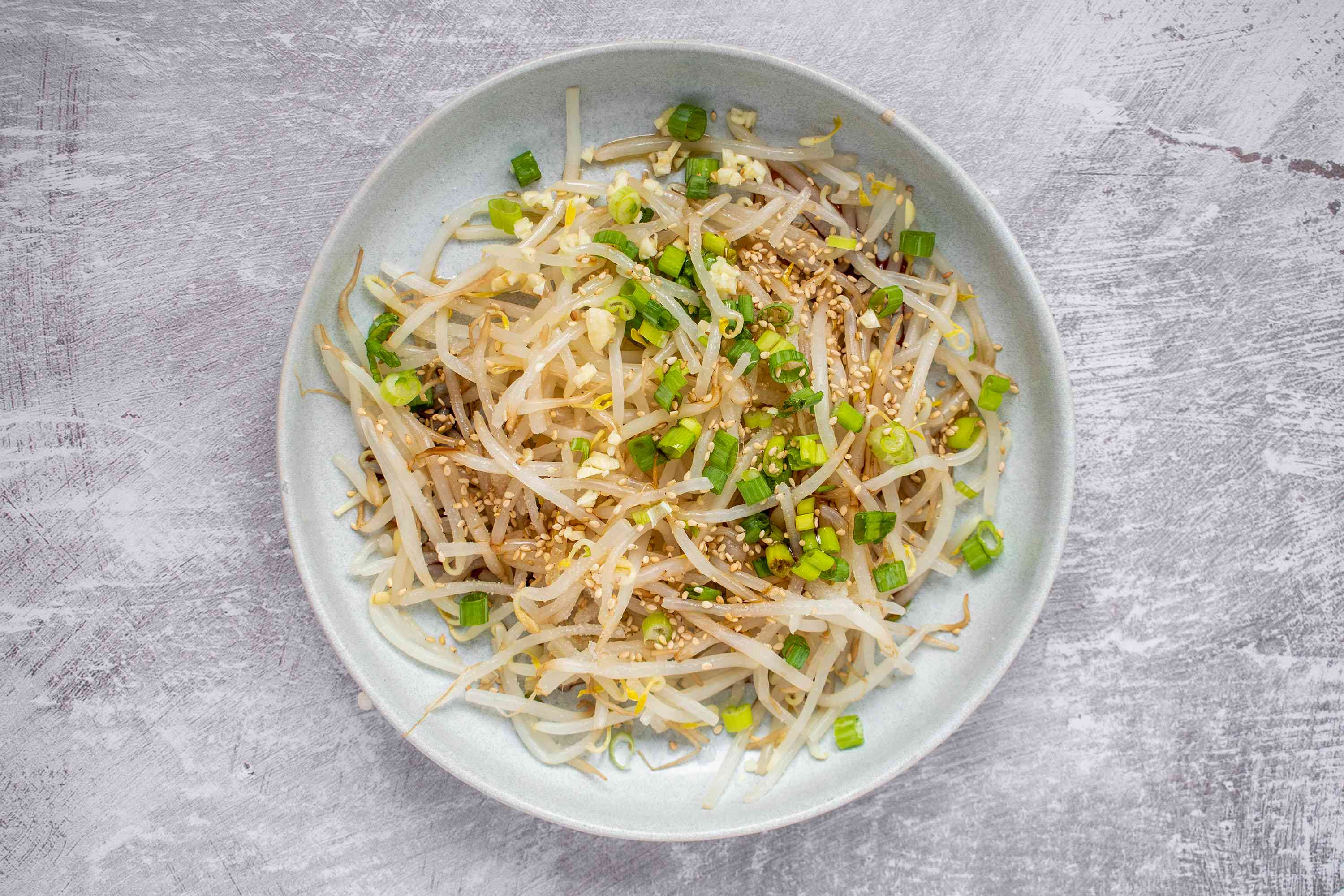 toss bean sprouts with other ingredients to make Korean Bean Sprout Salad (Sookju Namul)