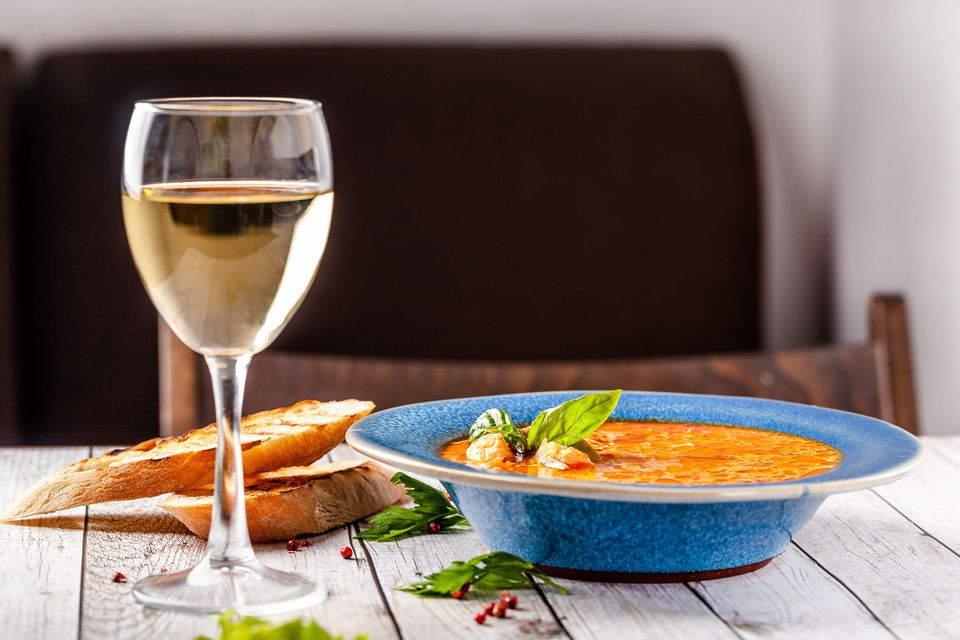 Spicy fish soup in bowl and white wine in glass