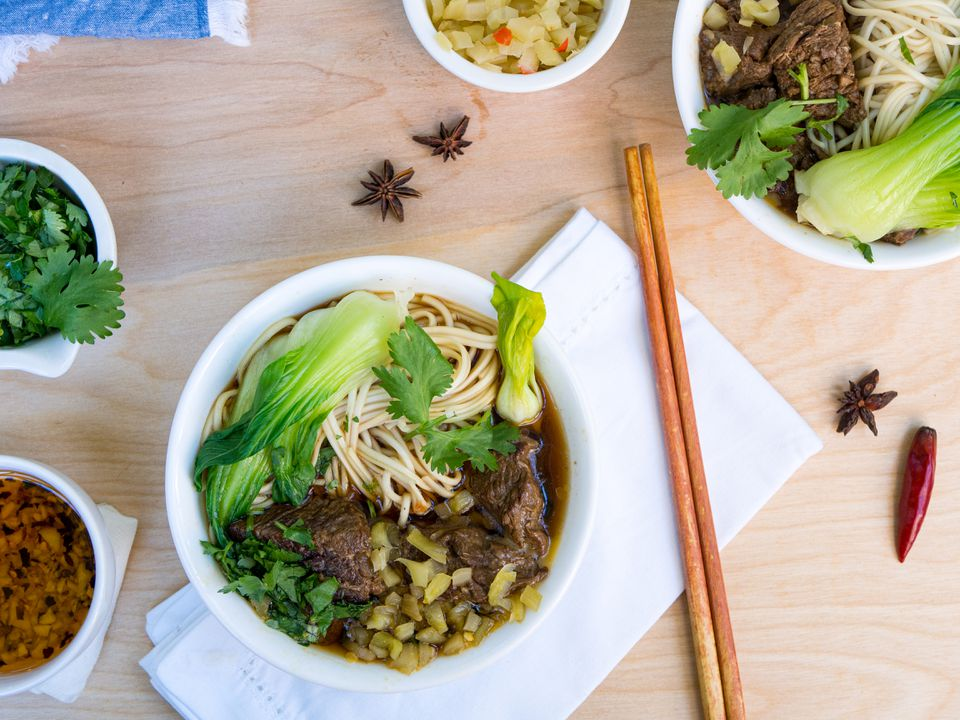 bowls of taiwanese beef noodle soup on table with chopsticks