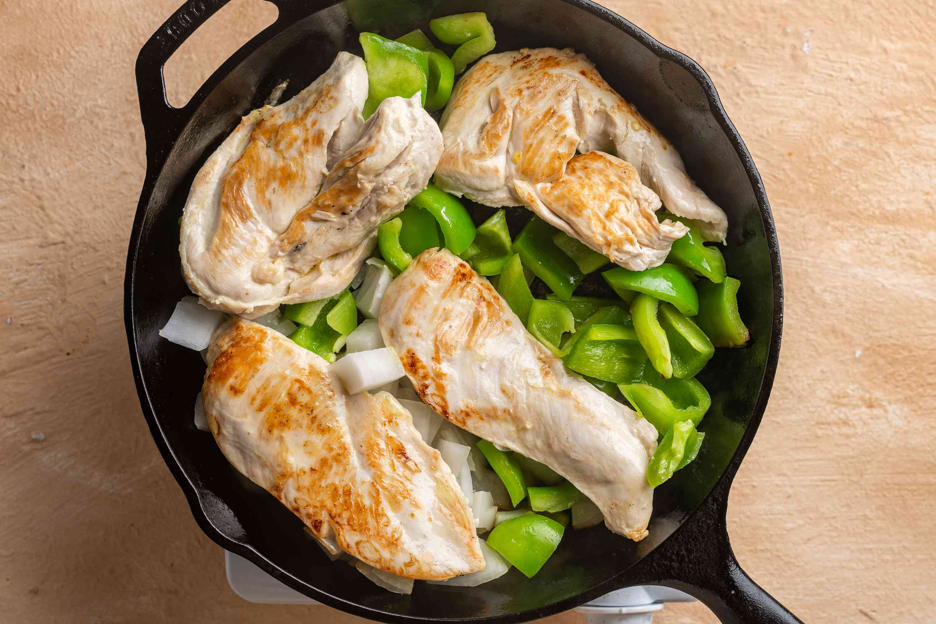 chicken breasts, onion, and bell pepper in a skillet