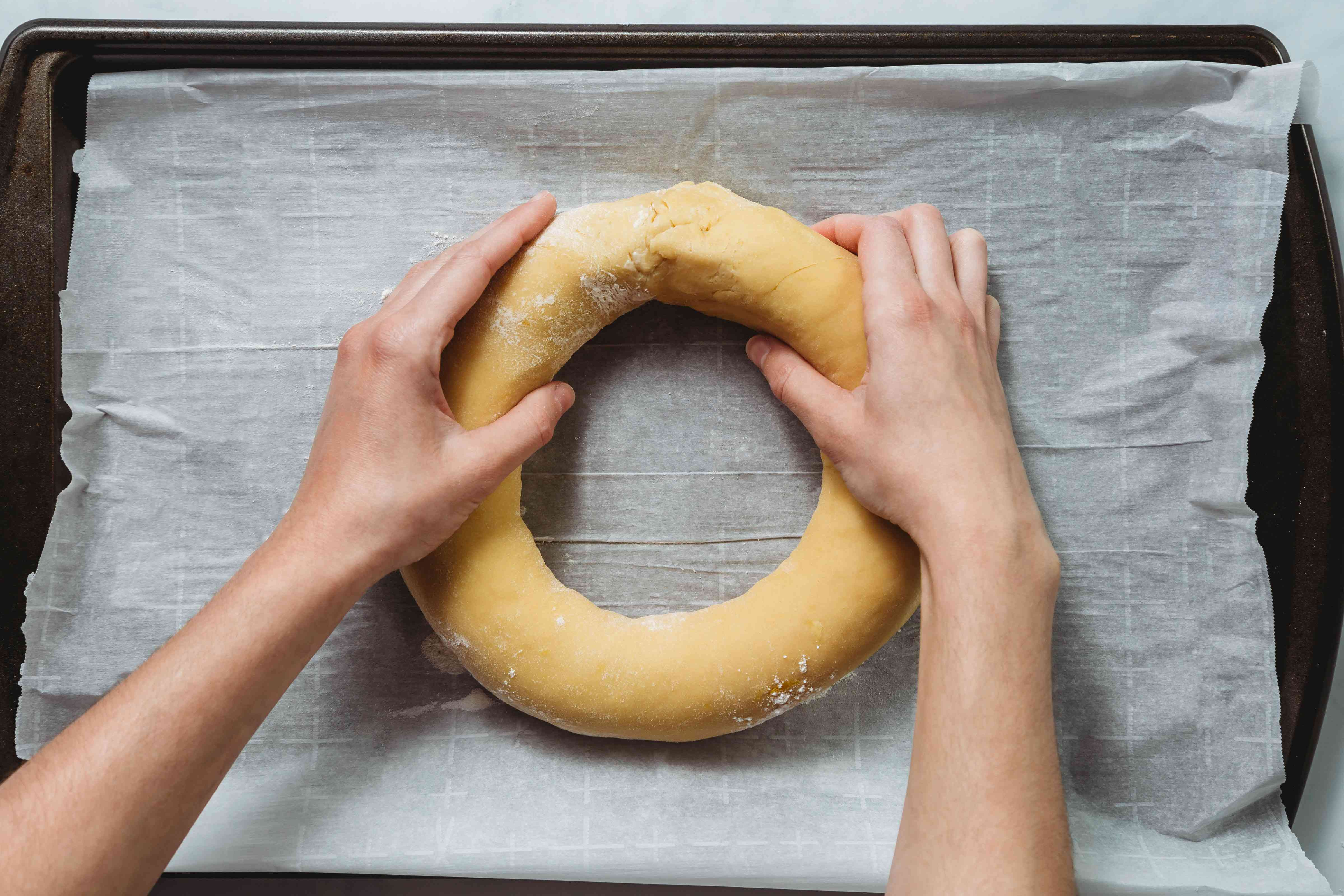 dough being shaped into ring on baking sheet