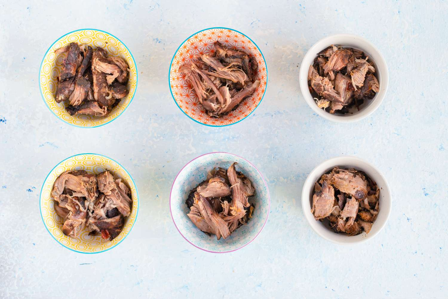 Cooked birria beef in bowls