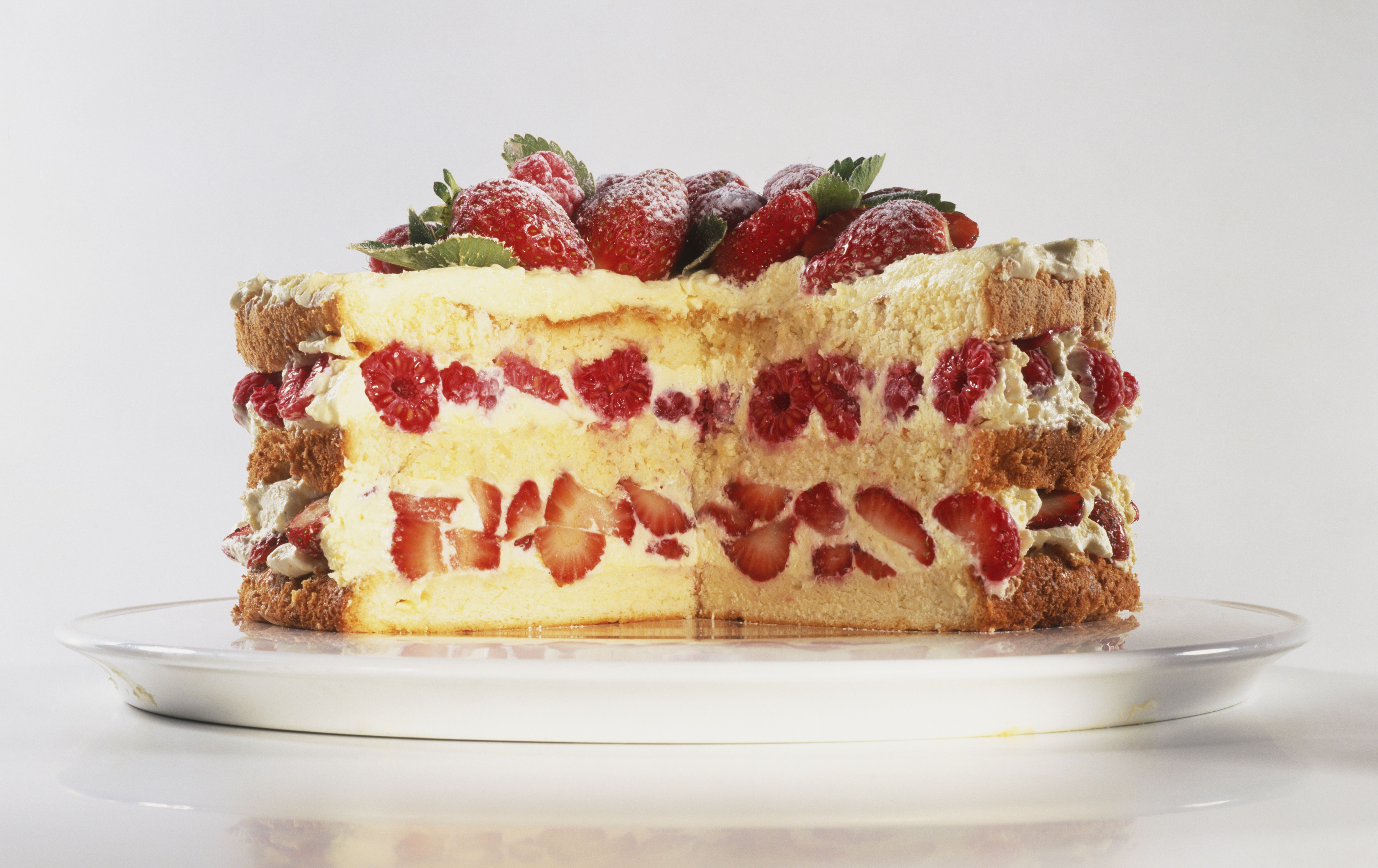 Biscuit de Savoie, layered cream, strawberry and raspberry cake with slice removed, front view