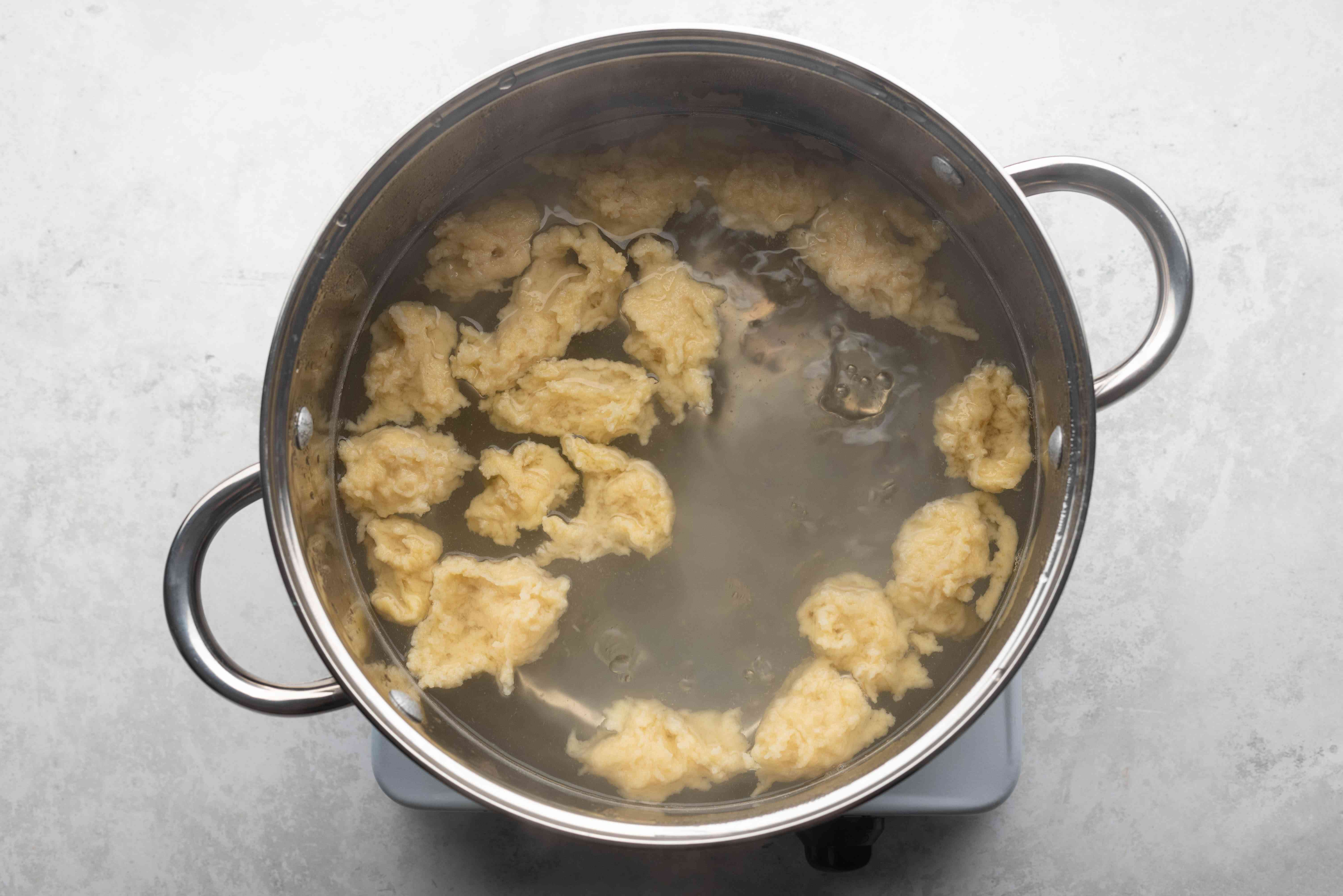 dumpling cooking in a pot with water