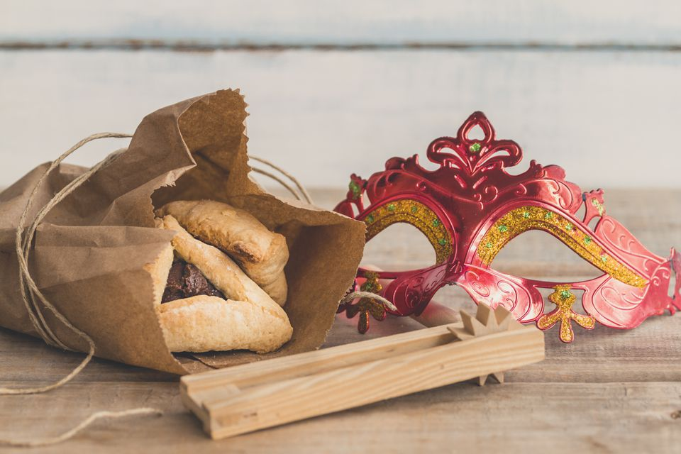 Purim jewish holiday composition with hamantaschen, purim mask and purim gragger on a vintage wood background with copy space'r'n
