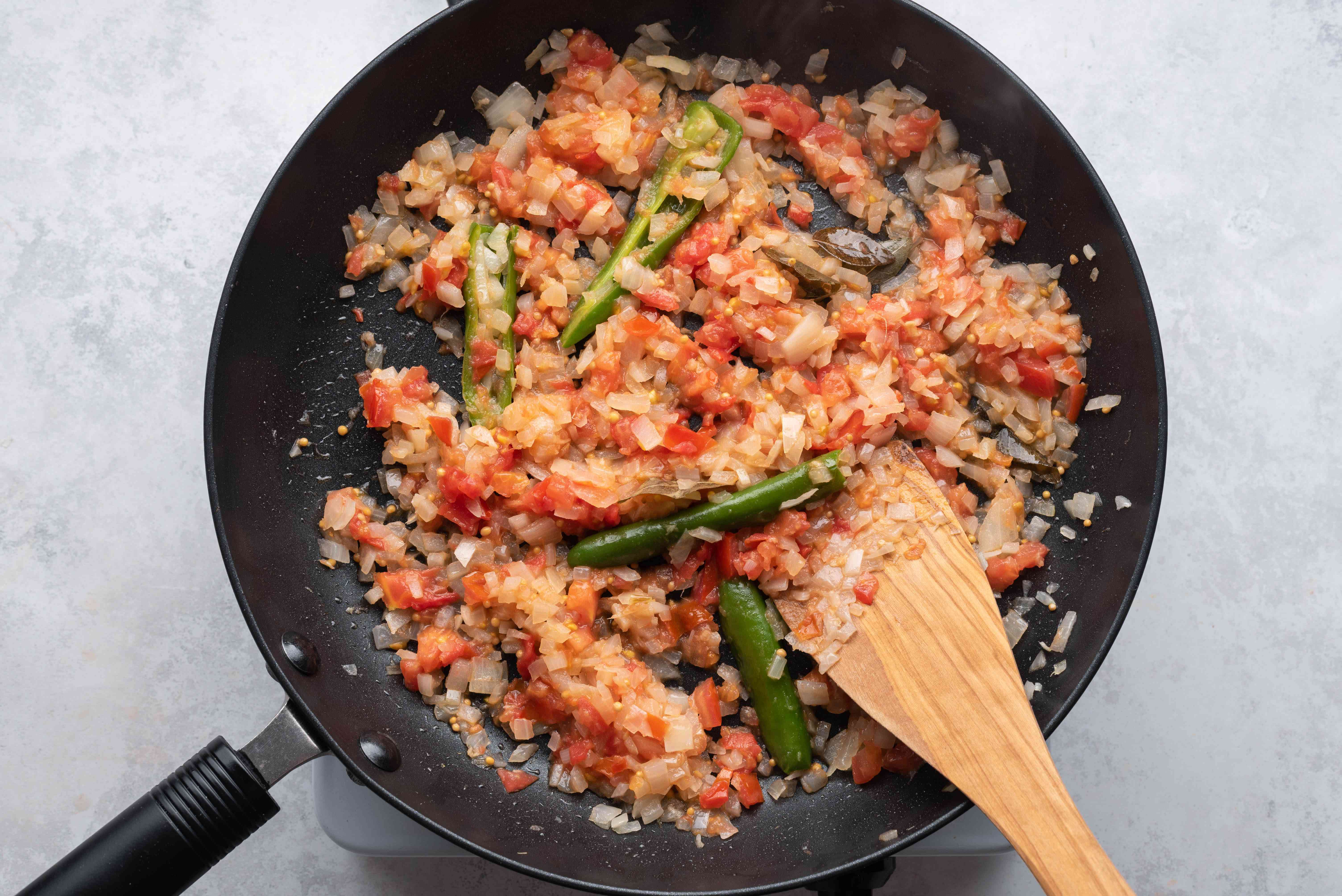 add tomatoes to the onion and spice mixture in the pan