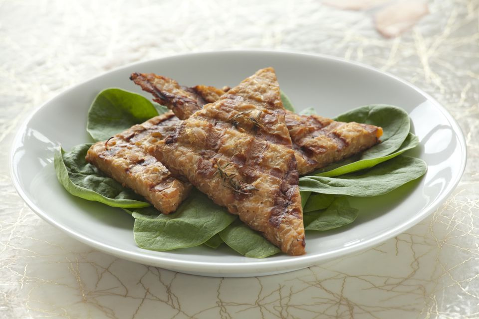 Close up of grilled tempeh served over greens
