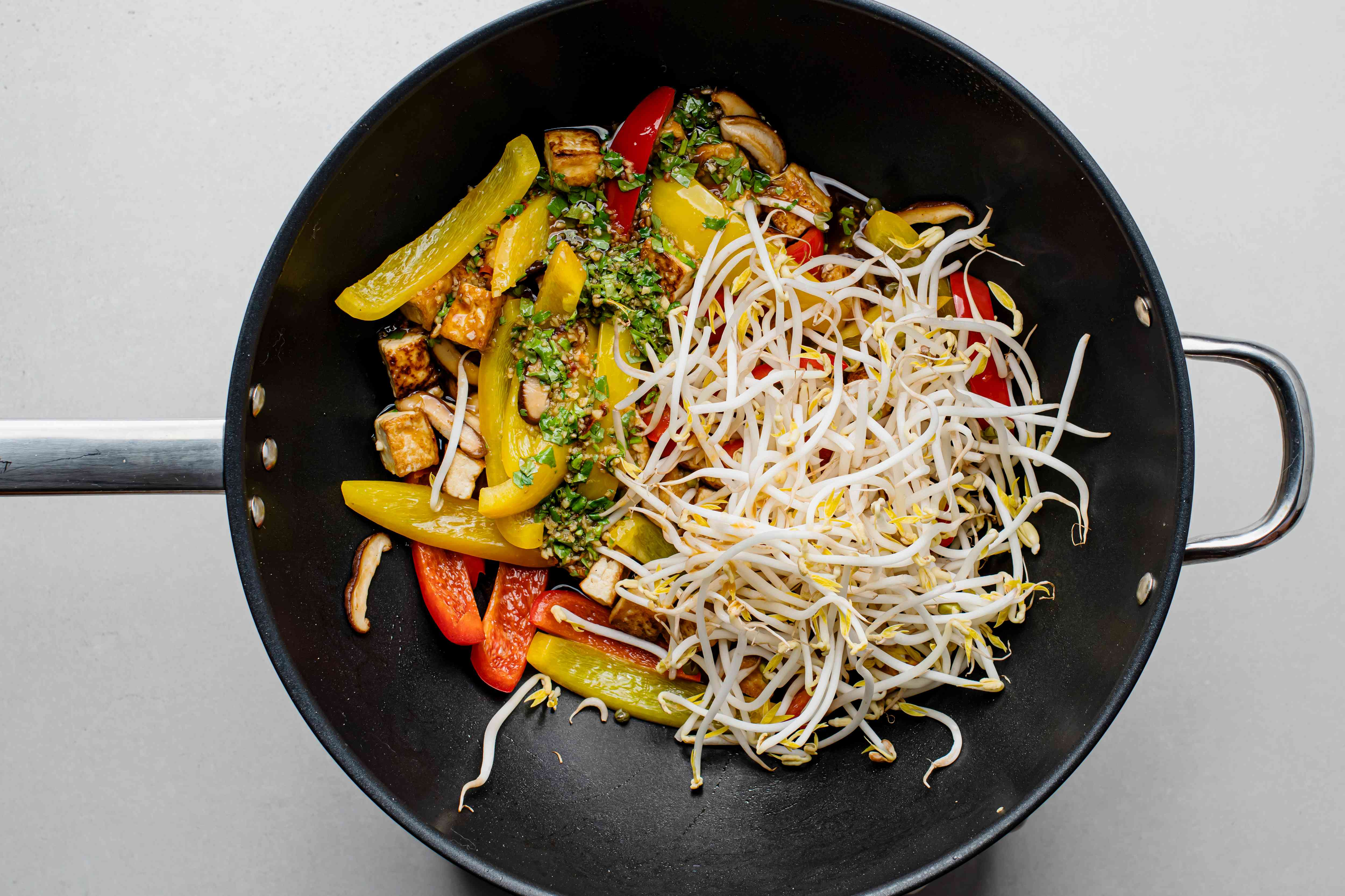 mung beans sprouts and the stir-fry sauce added to peppers and tofu in the wok