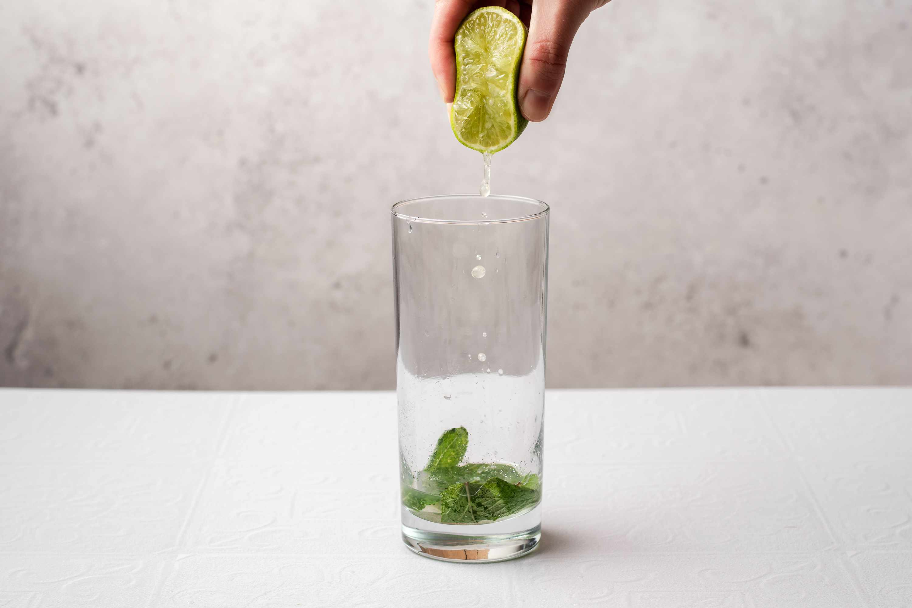 squeeze lime into the glass with the mint