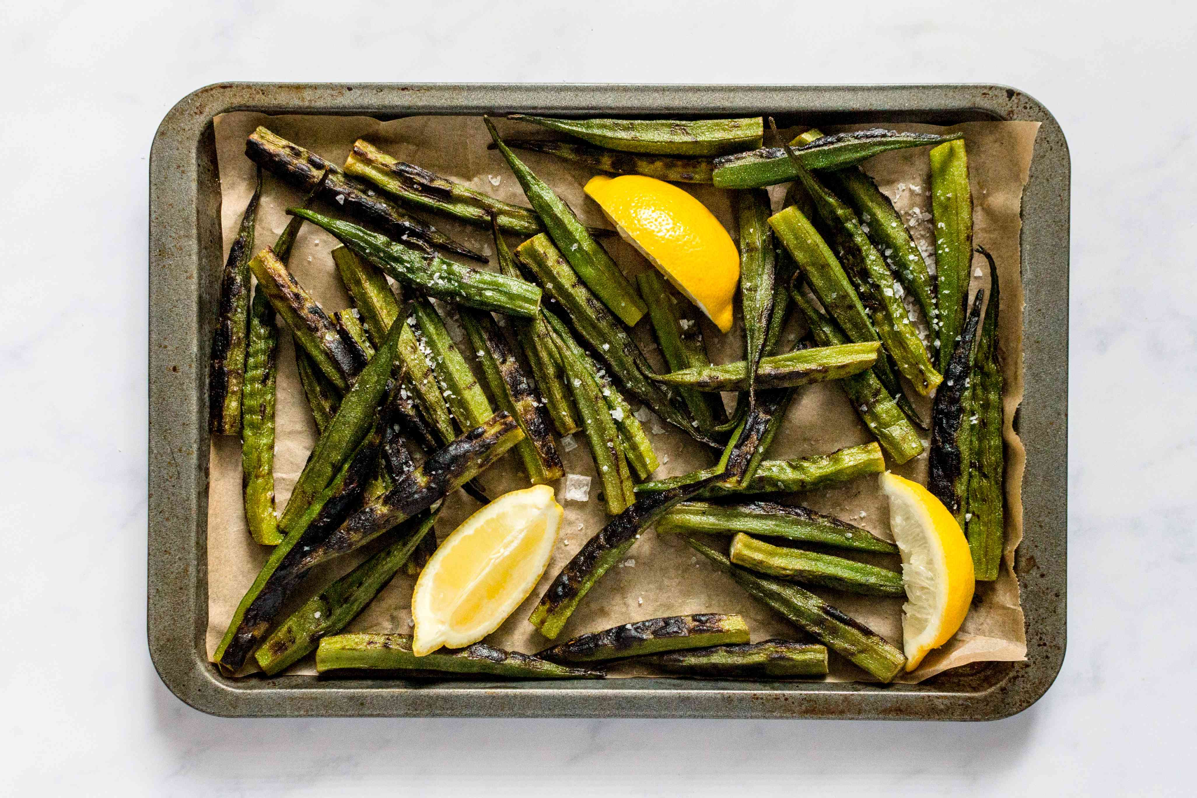 Grilled Okra and lemons on a baking sheet