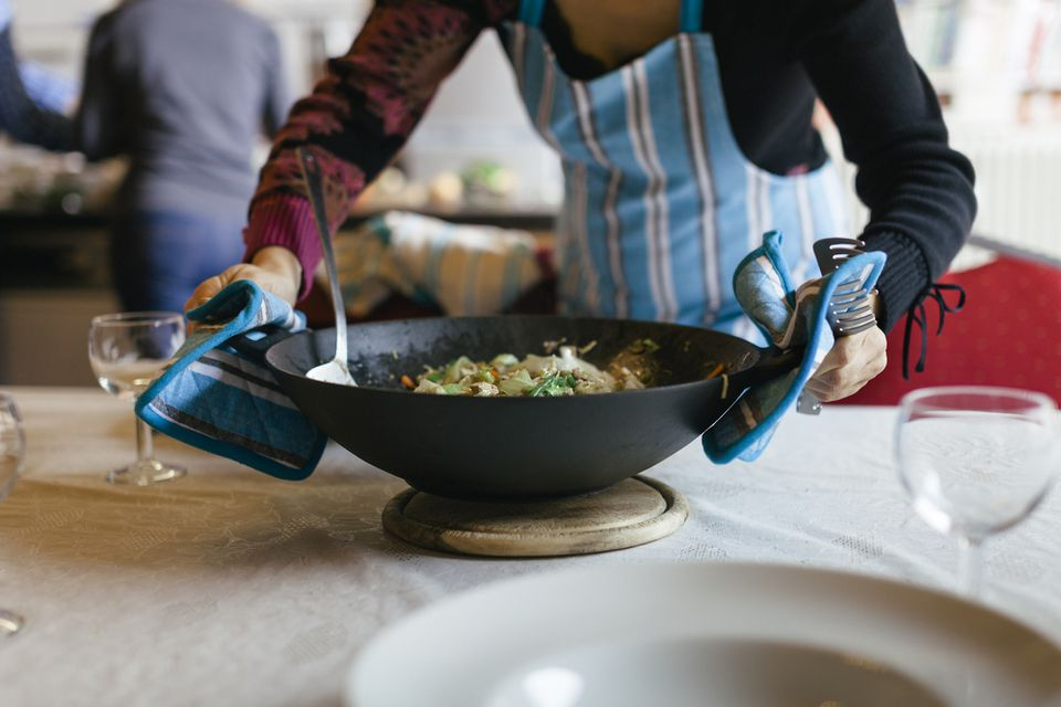 Cooking wok being placed on a table with oven mitts