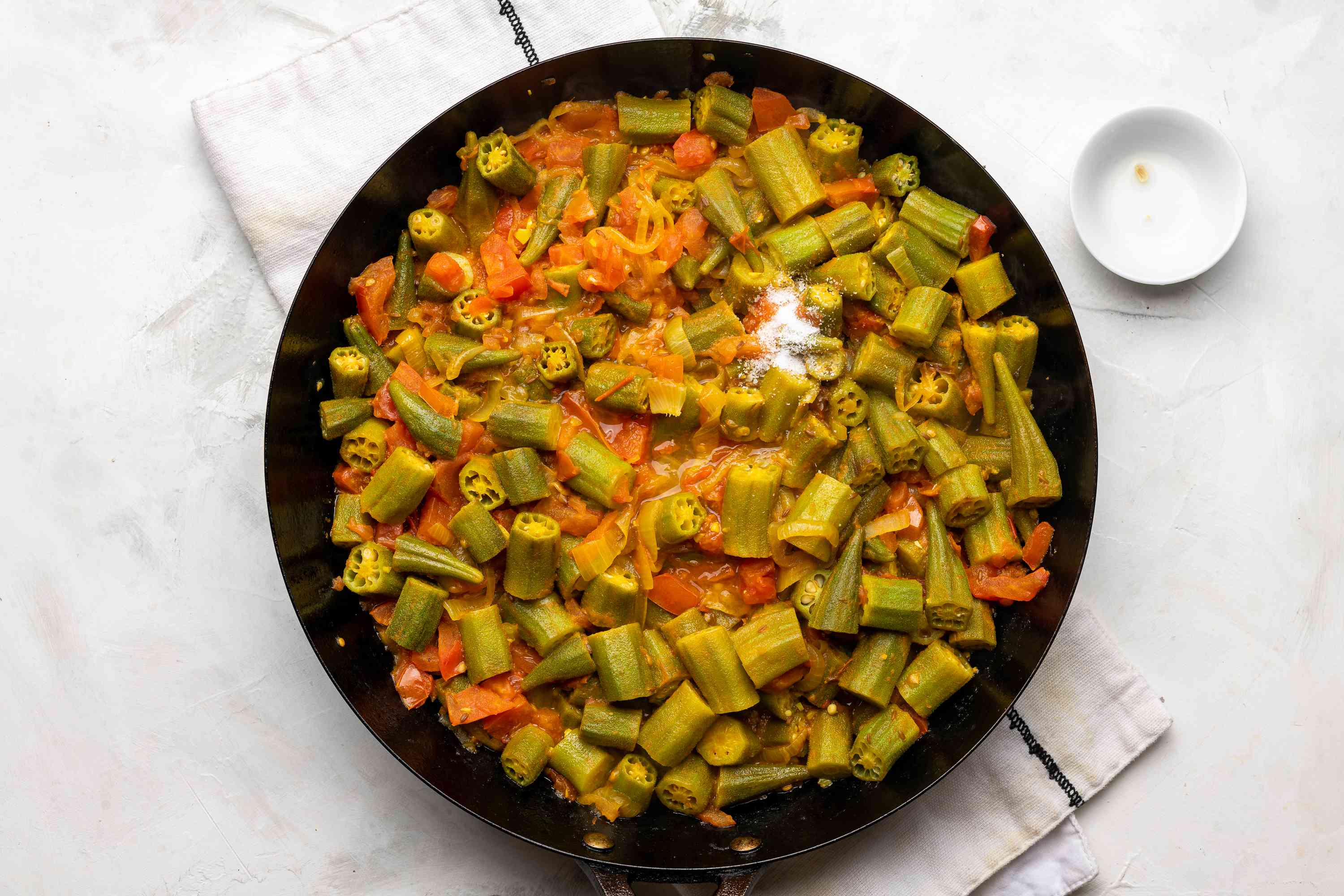 salt and lemon juice added to the okra mixture in the pan