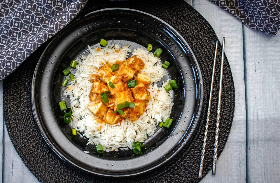 Tofu with peanut sauce, rice and scallions on a black plate with black placemat, silver chopsticks and black napkns.