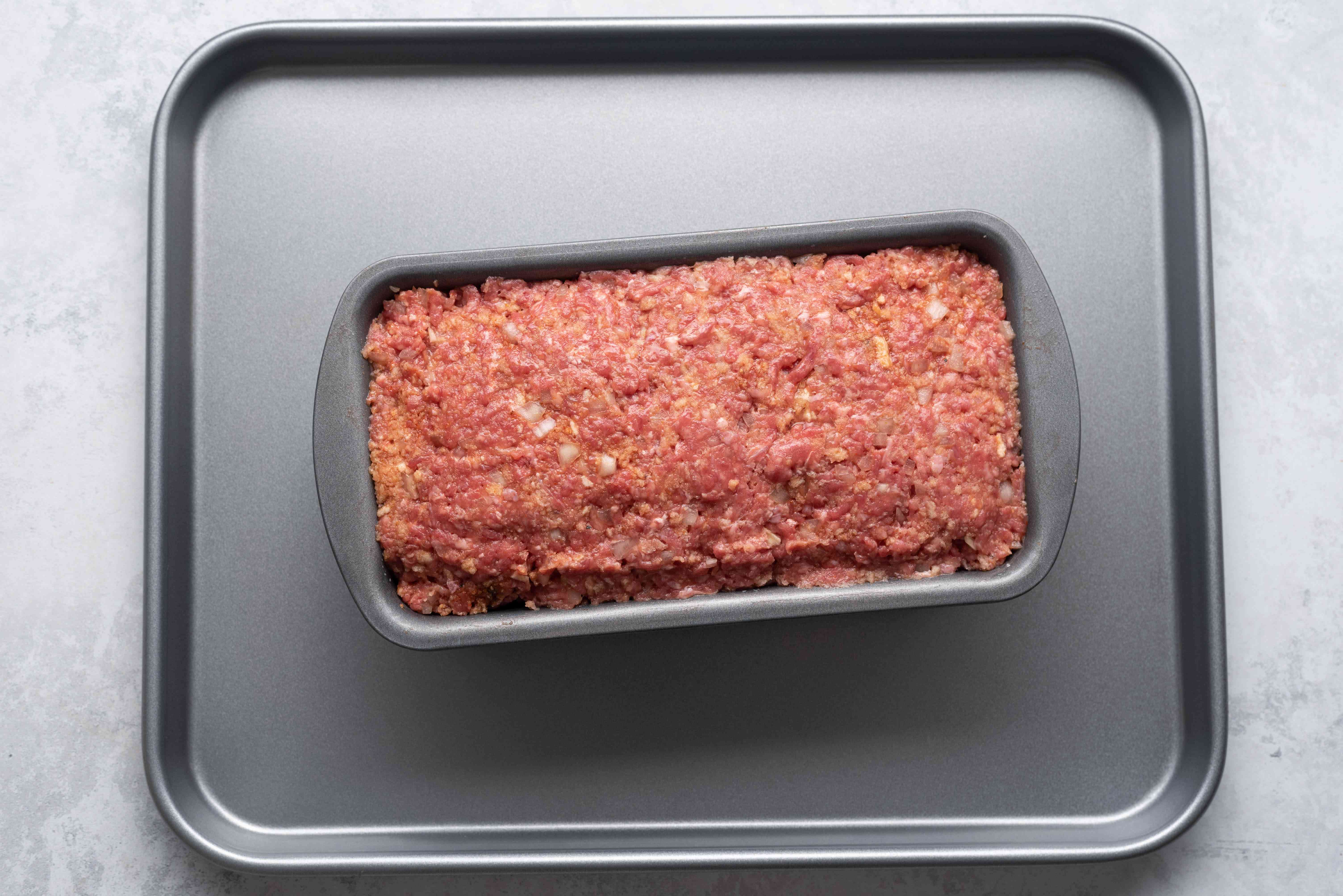 Raw meatloaf in a loaf pan on a baking sheet