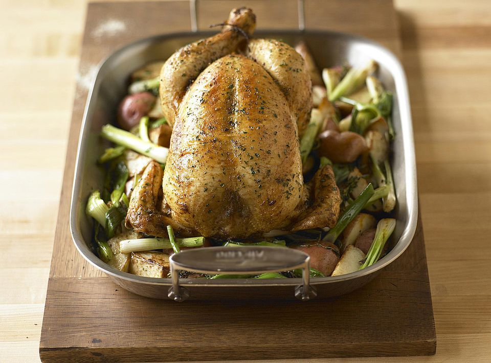 A roast chicken on top of vegetables