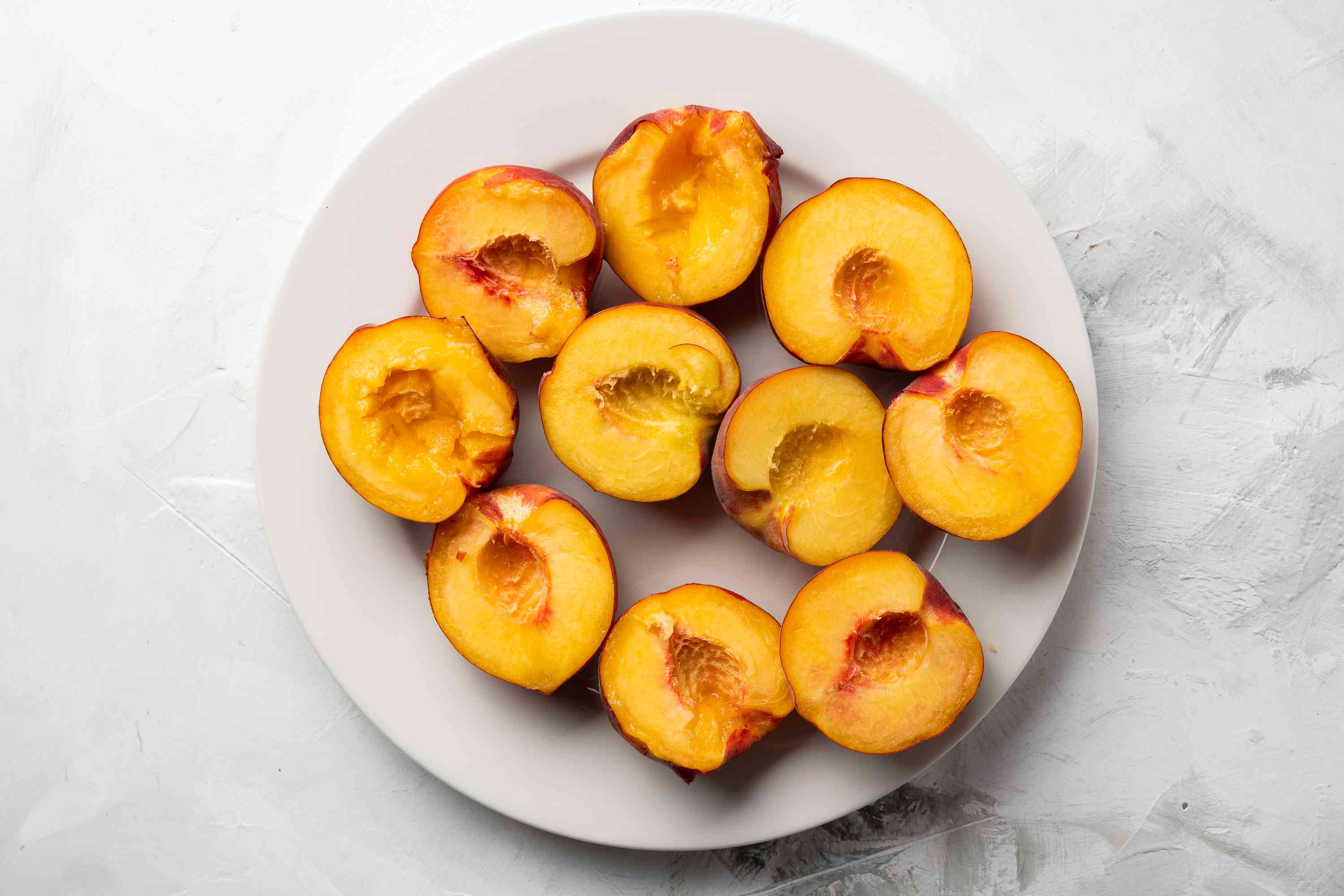 Cut the peaches in half and pit them
