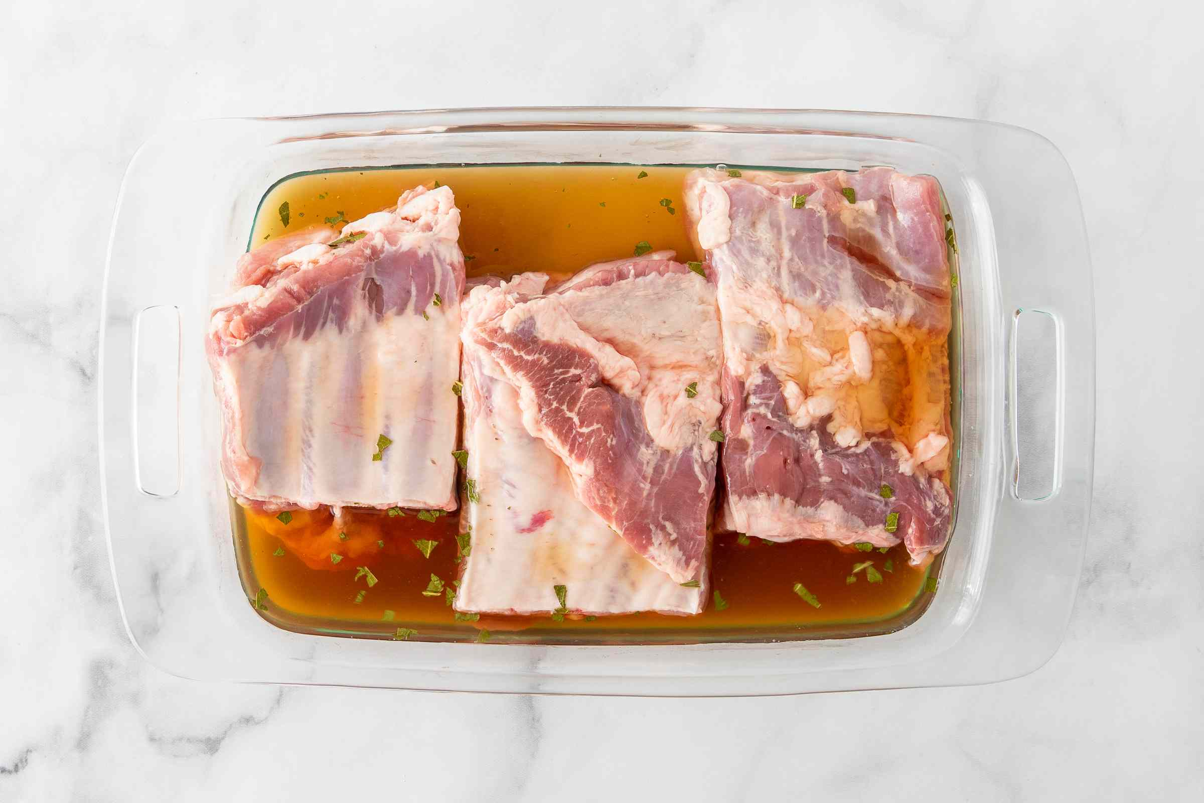 spareribs and marinade in a container
