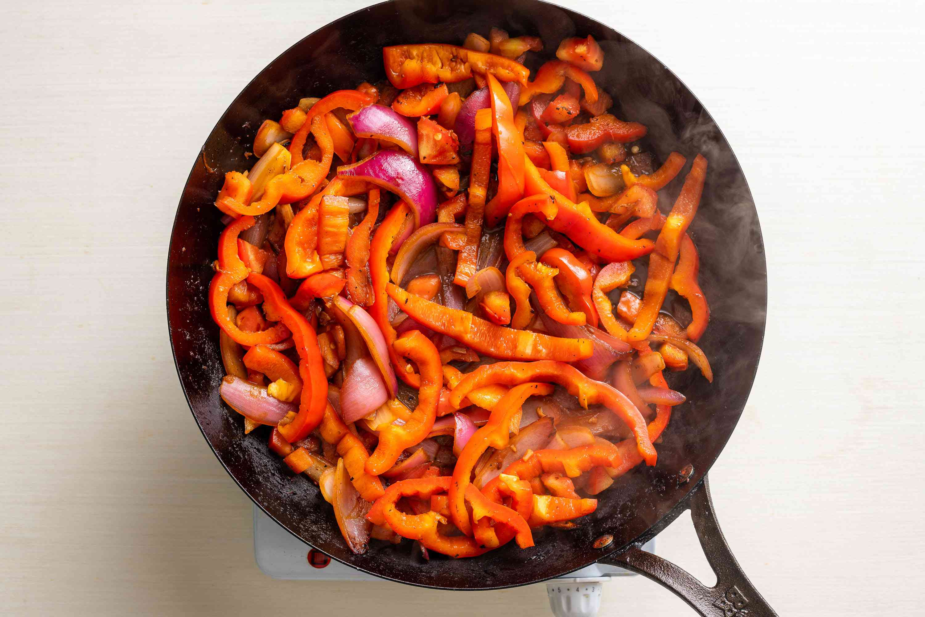 red peppers and tomato added to the pan