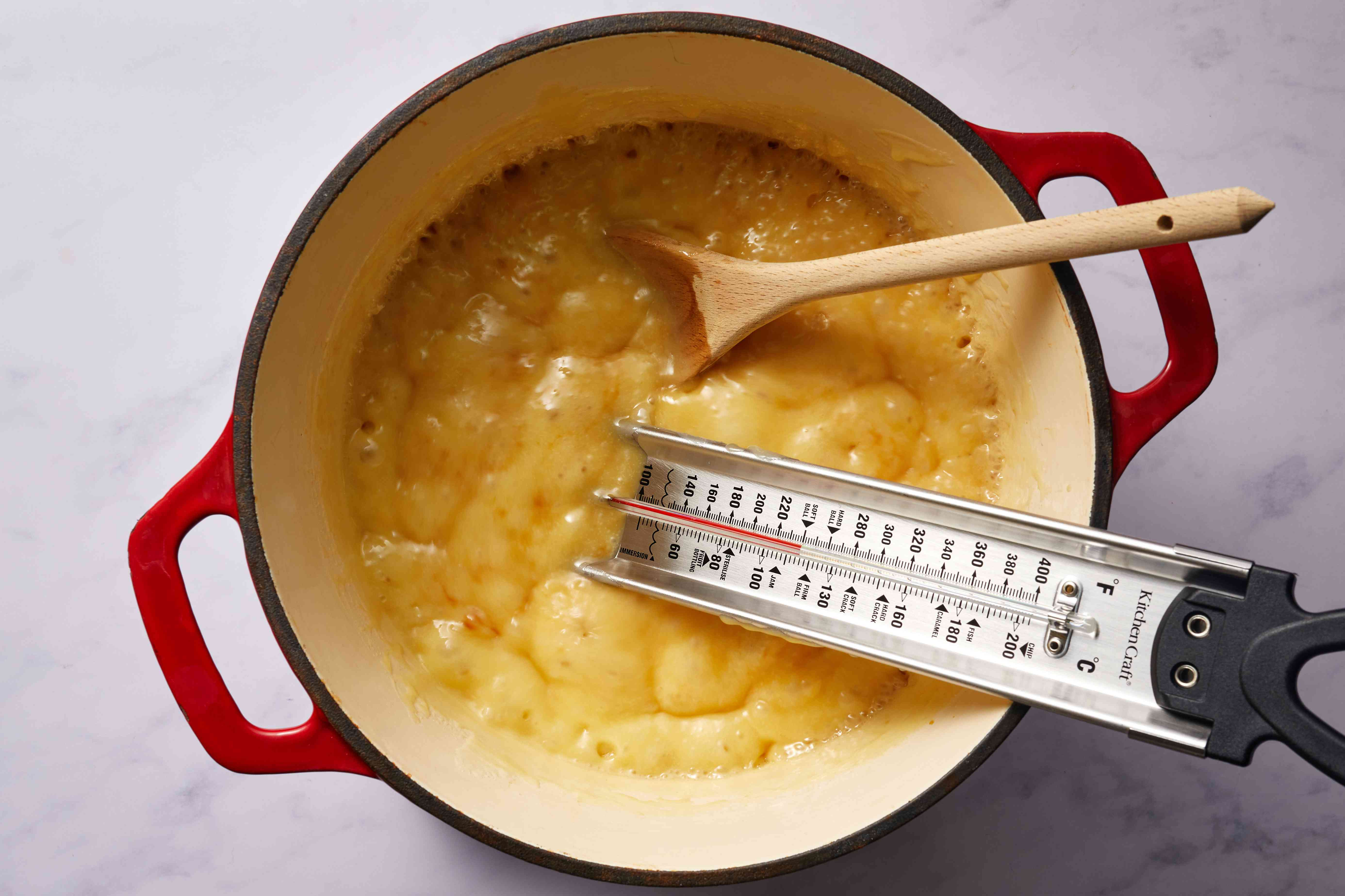 butter mixture cooking in a saucepan, thermometer